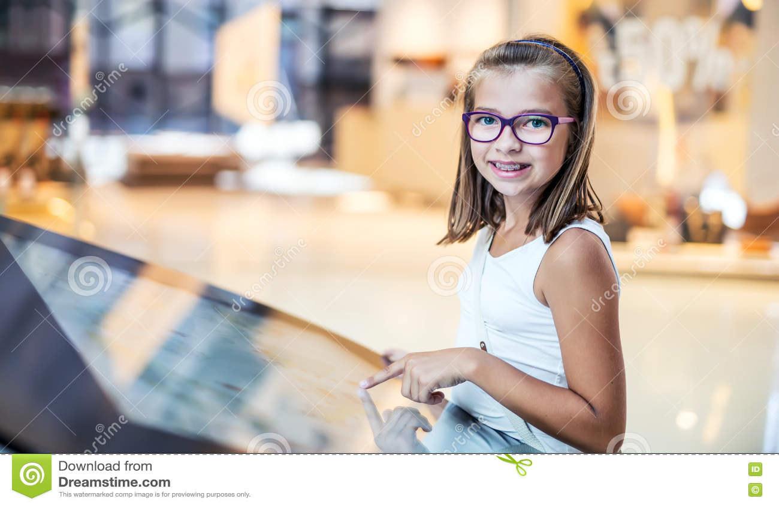 Niña linda hermosa que estudia plan de la orientación en alameda de compras Guía de la tienda del centro comercial Tecnología mod