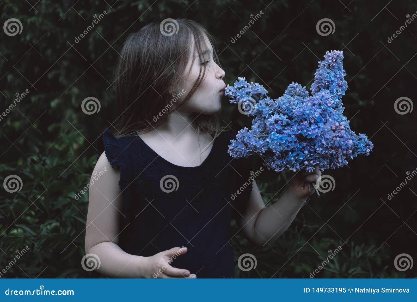 Niña linda que besa la lila