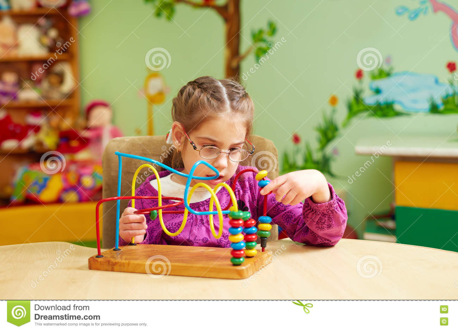 Niña linda que juega con el juguete que se convierte en la guardería para los niños con necesidades especiales