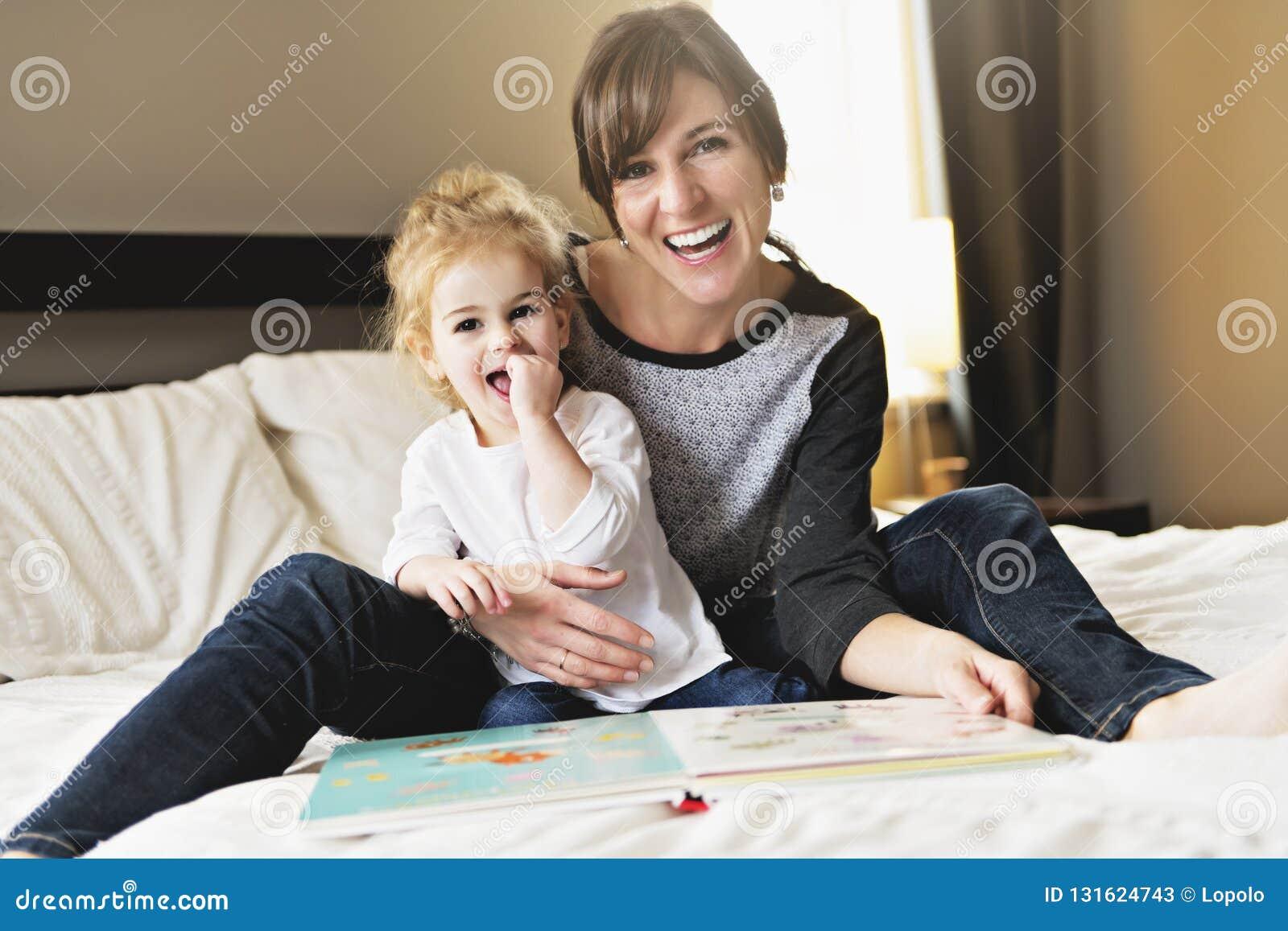 Niña linda que lee un libro con su madre en el dormitorio