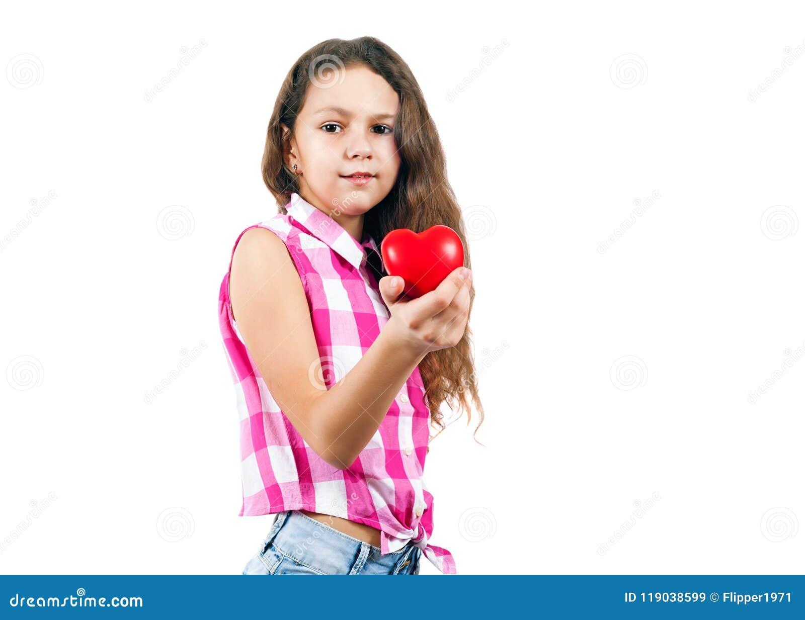 Niña linda que lleva a cabo un corazón