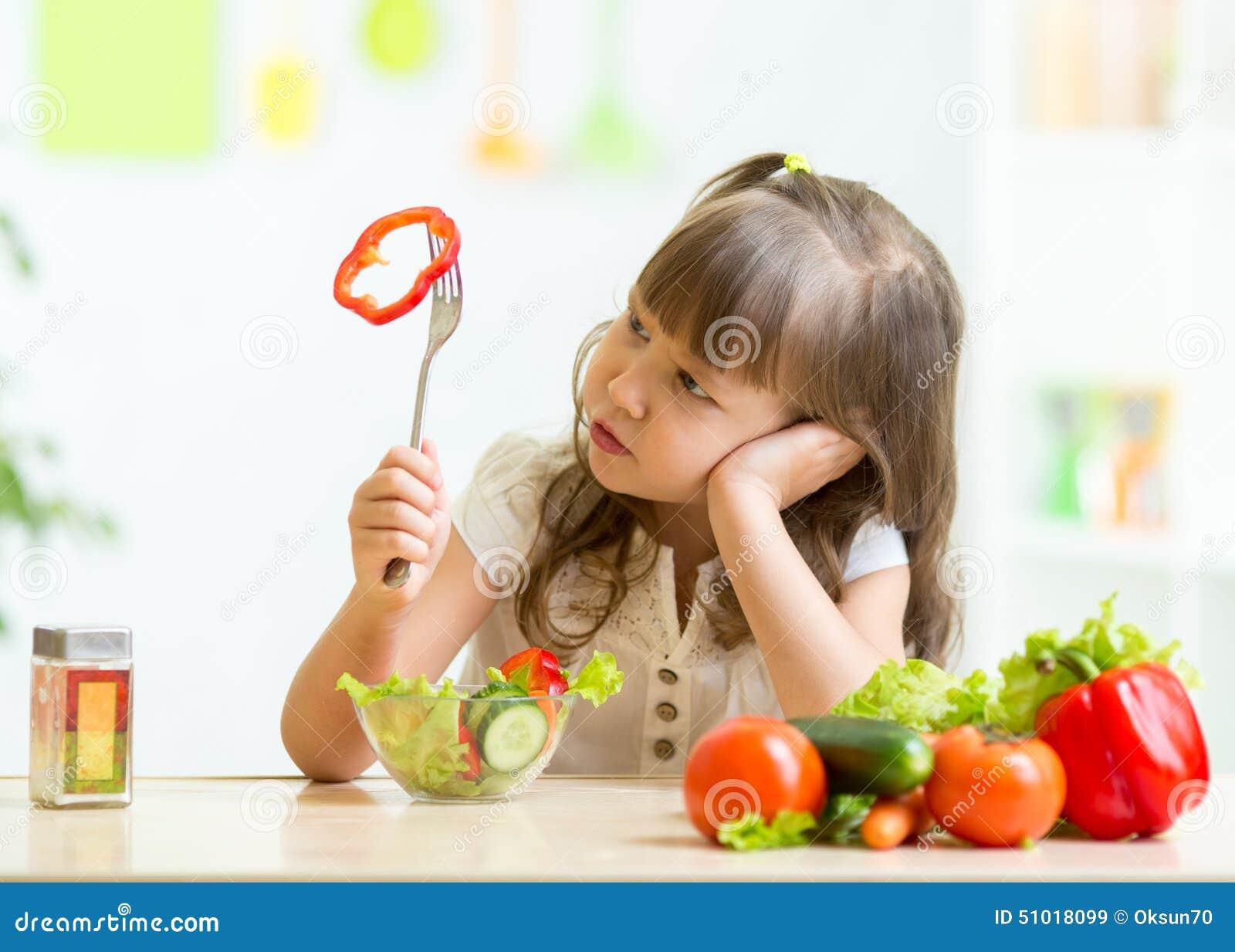 Niña linda que no quiere comer la comida sana