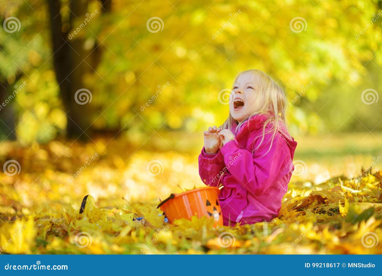 Niña linda que se divierte en día hermoso del otoño Niño feliz que juega en parque del otoño Niño que recolecta el follaje de oto