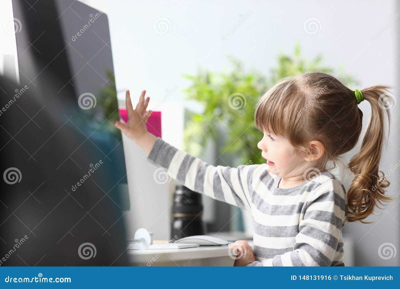 Niña linda que se sienta en casa en el funcionamiento de la mesa de trabajo con el ordenador