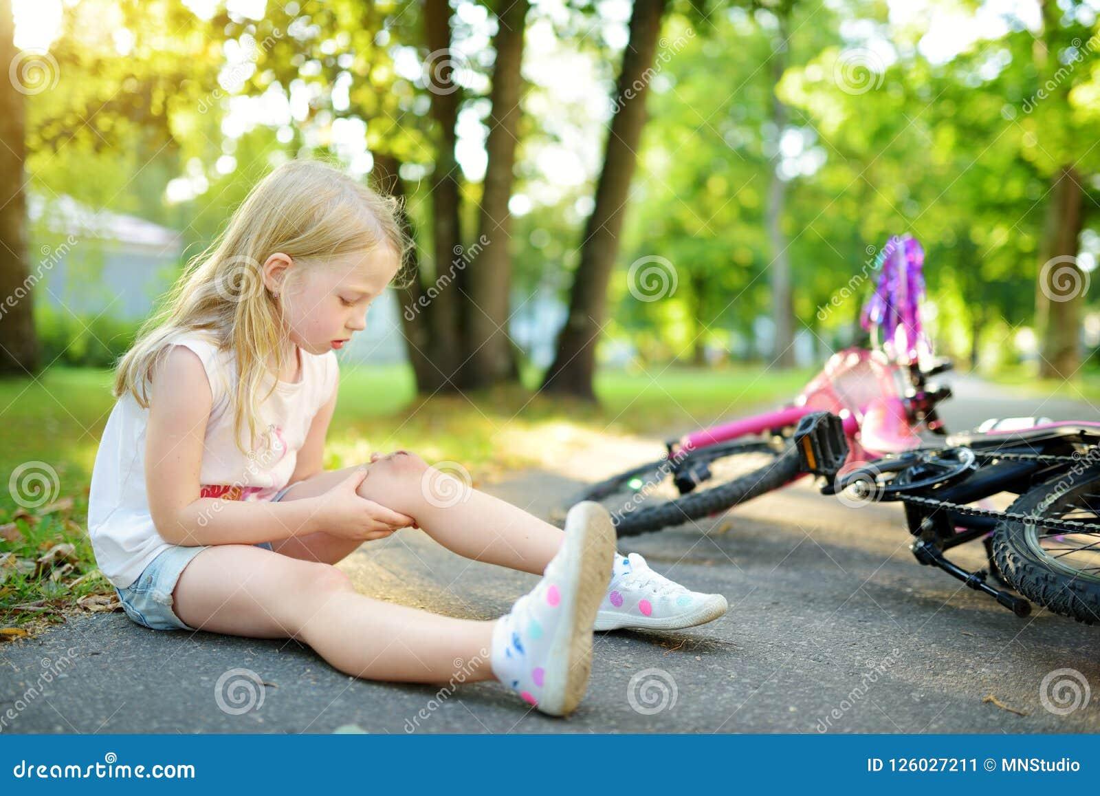 Niña linda que se sienta en la tierra después de caer apagado su bici en el parque del verano Niño que consigue daño mientras que
