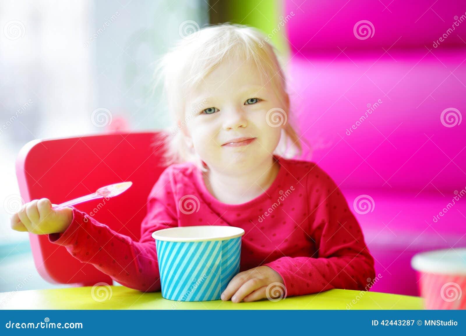 Niña pequeña adorable que come el helado