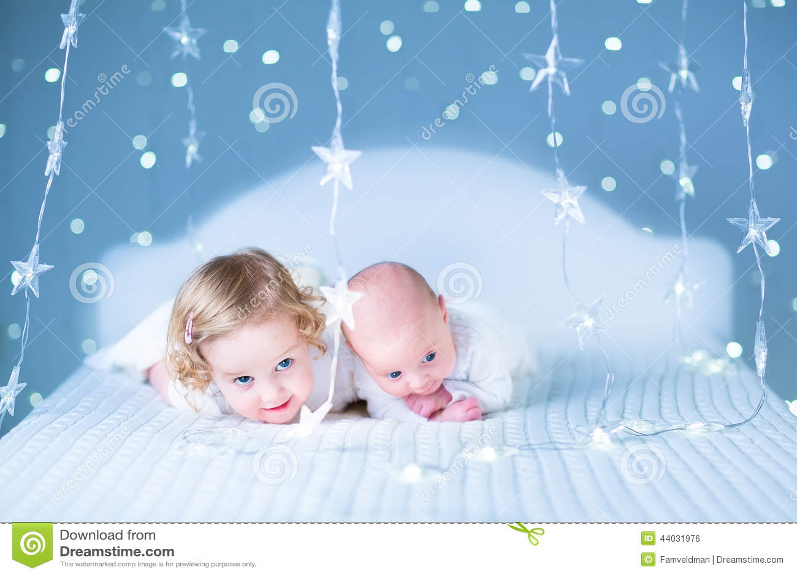 d7da90618dc Niña pequeña adorable y su hermano recién nacido del bebé en luces  alrededor de ellas