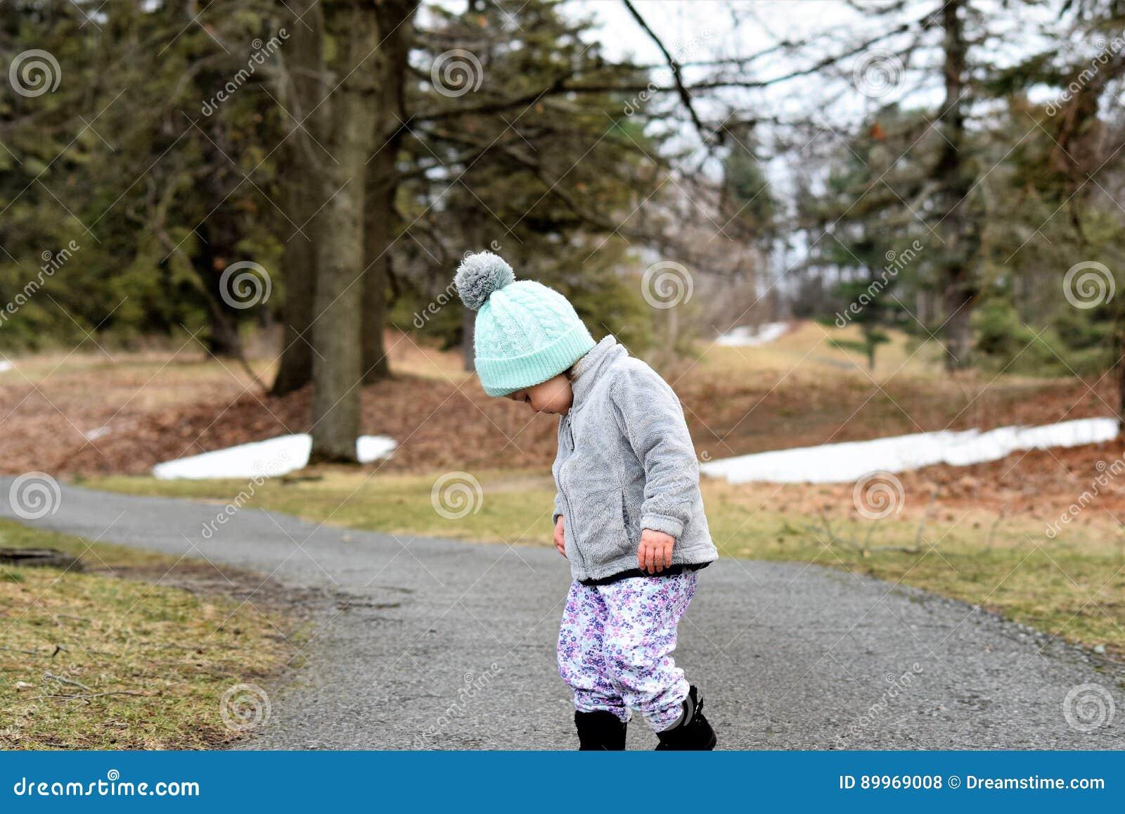 Niña pequeña en la trayectoria selvática que mira abajo