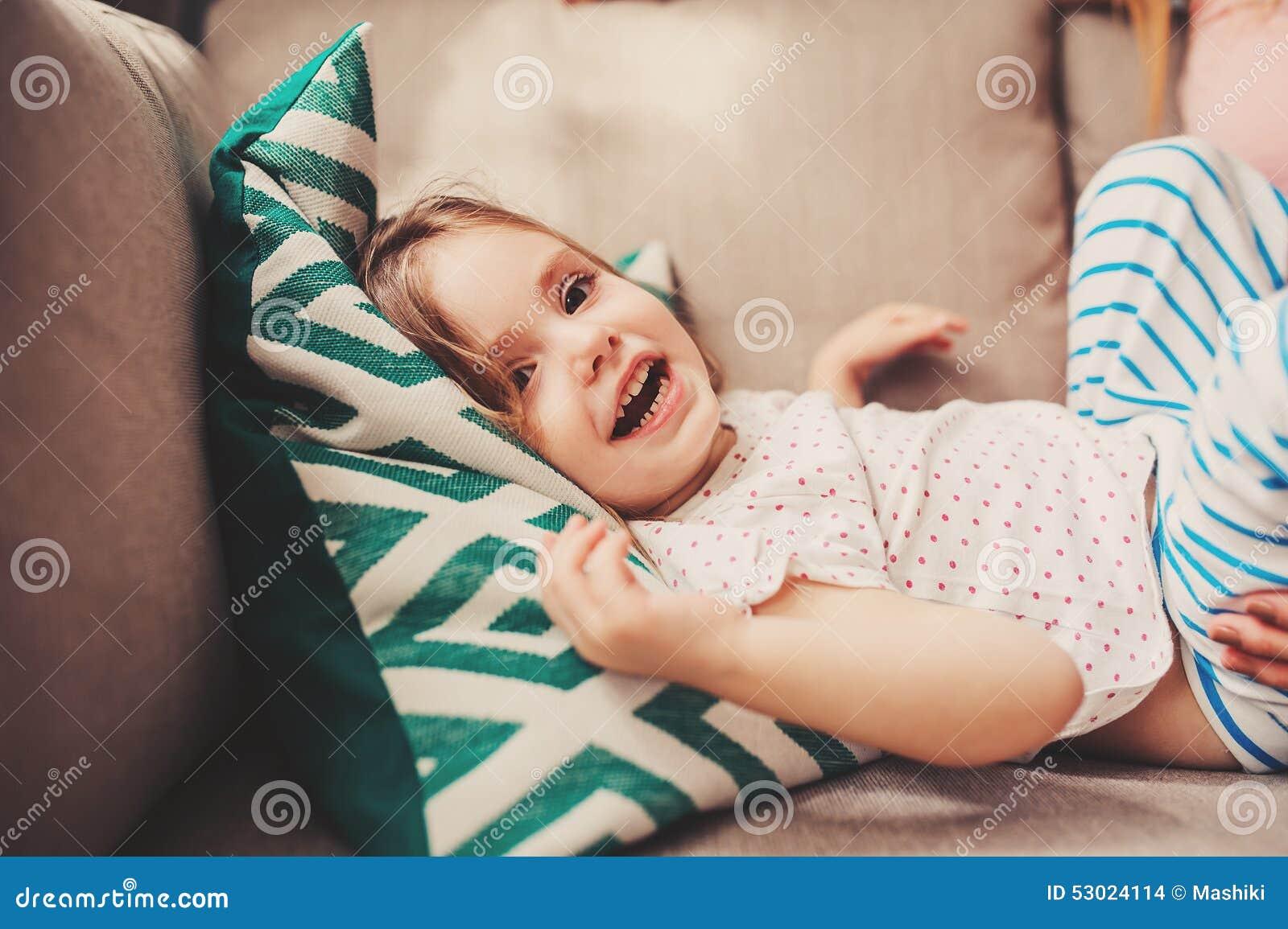 Niña pequeña feliz linda que se divierte en casa