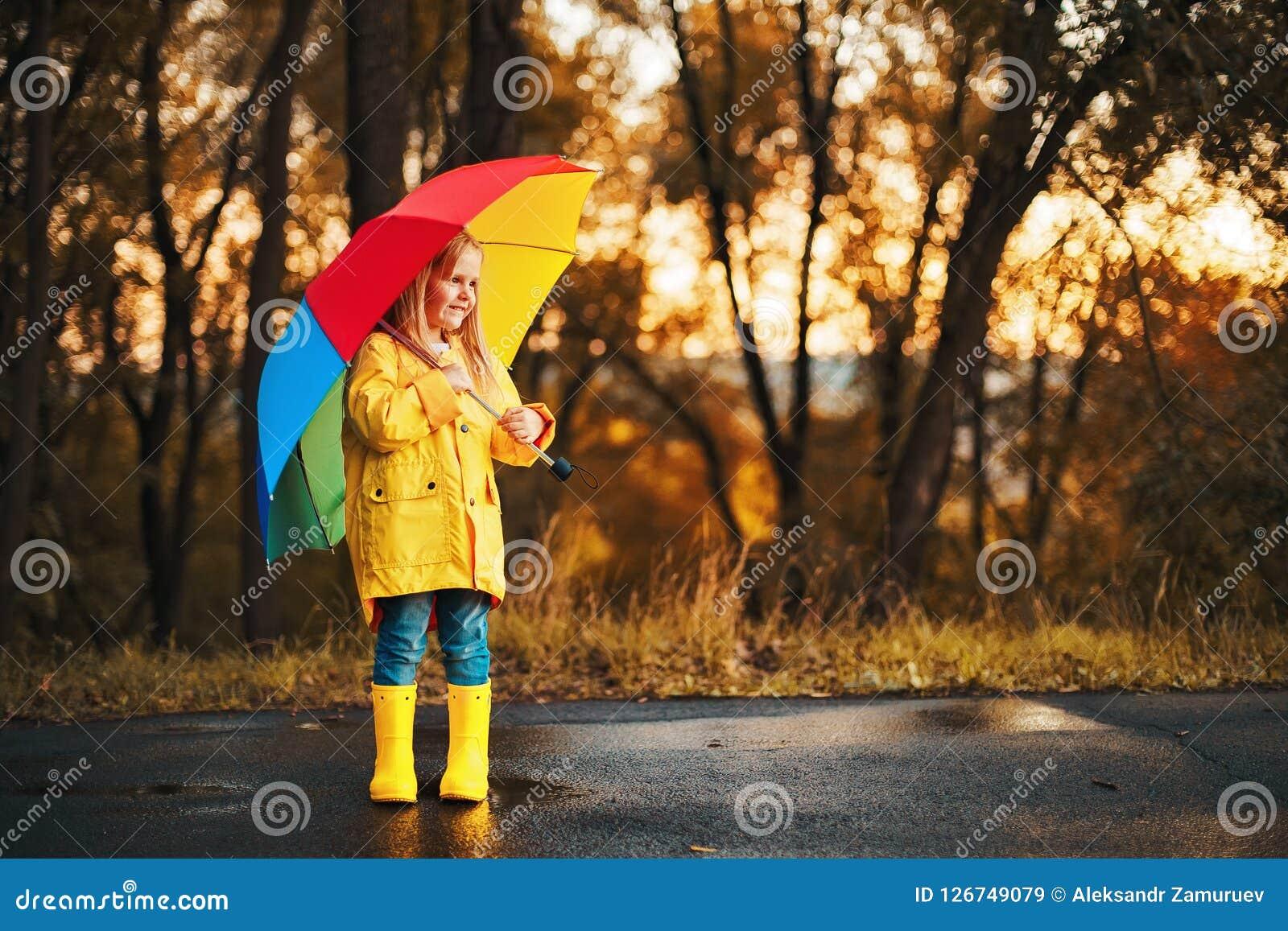 Niña pequeña linda divertida que lleva la capa impermeable con el paraguas colorido