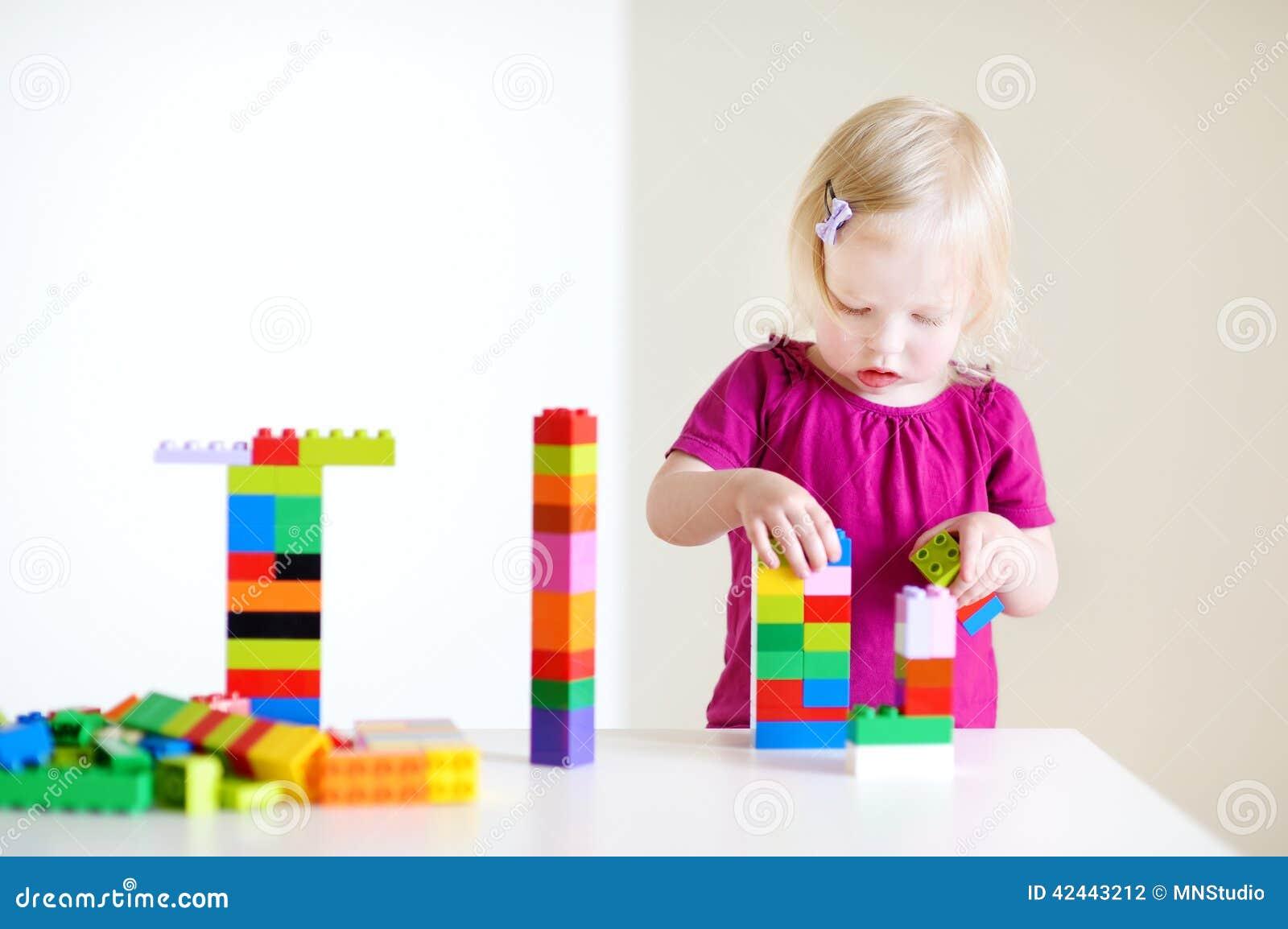 Niña pequeña linda que juega con los bloques coloridos