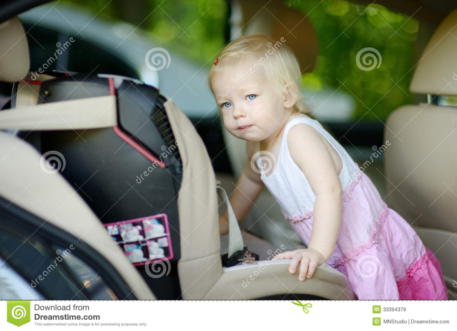 Niña pequeña que consigue en un asiento de carro