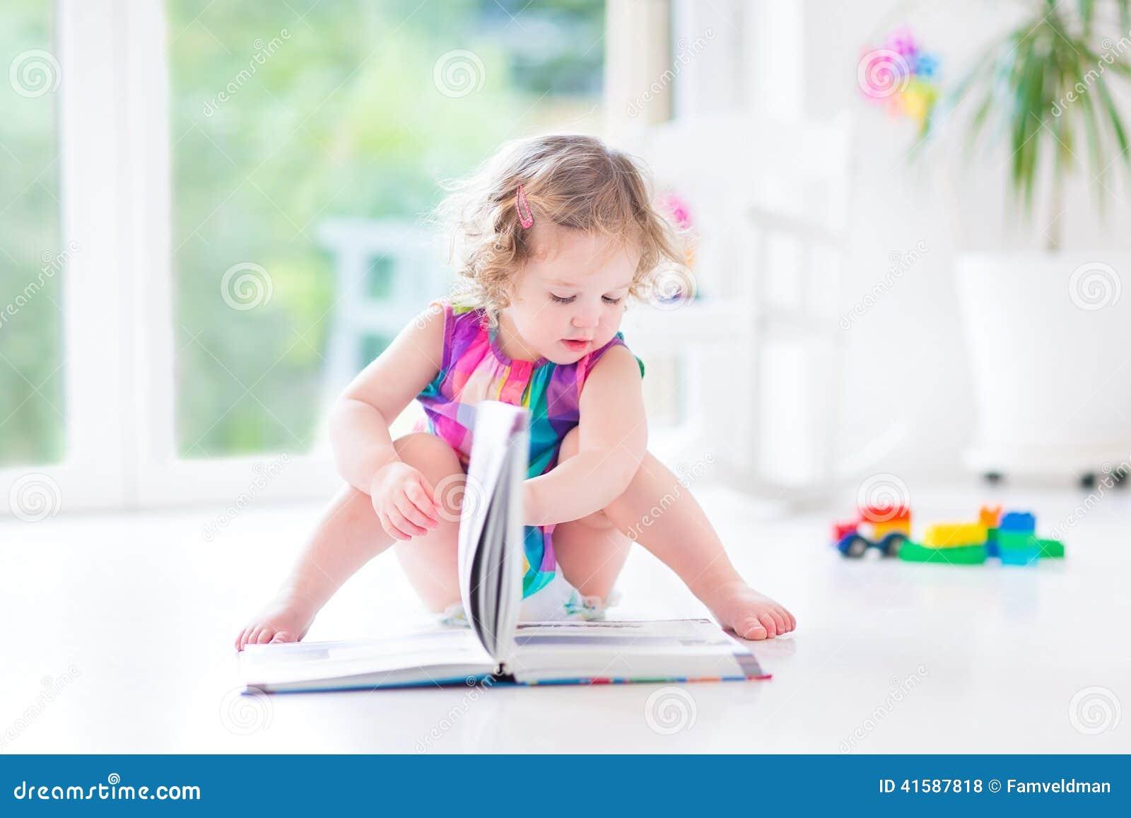 Niña pequeña rizada divertida en libro de lectura rosado del vestido