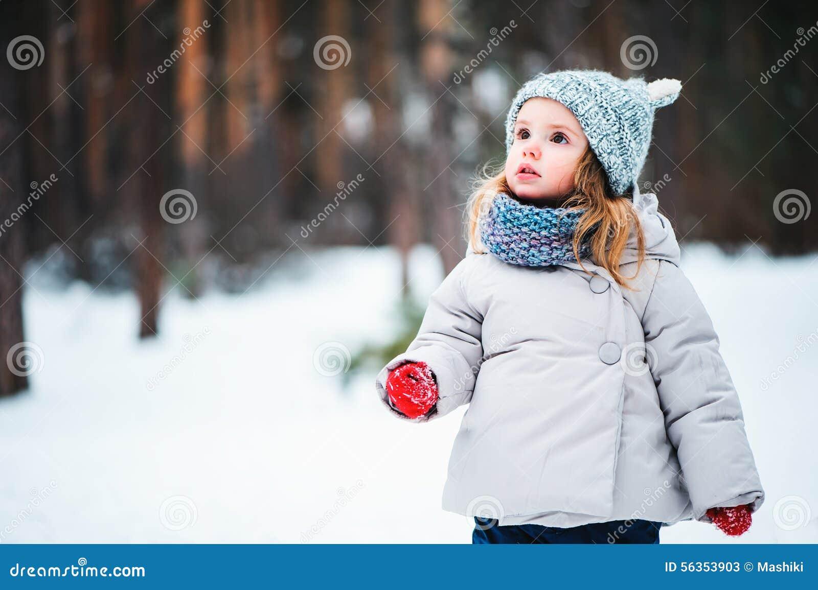 Niña pequeña soñadora linda que camina en bosque del invierno