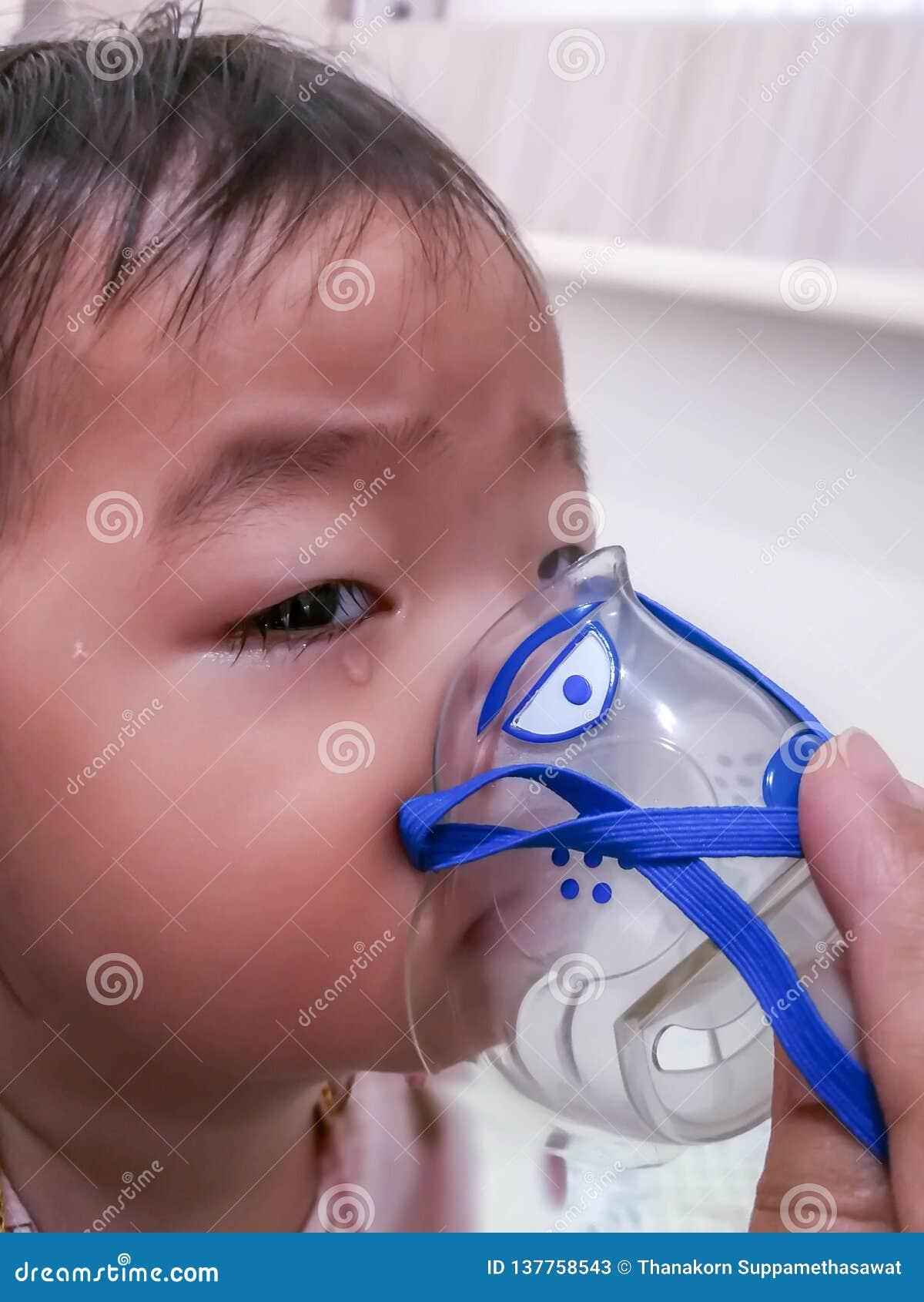 Niña que hace la inhalación con el nebulizador en casa concepto enfermo de la tos del vapor del nebulizador de la inhalación del