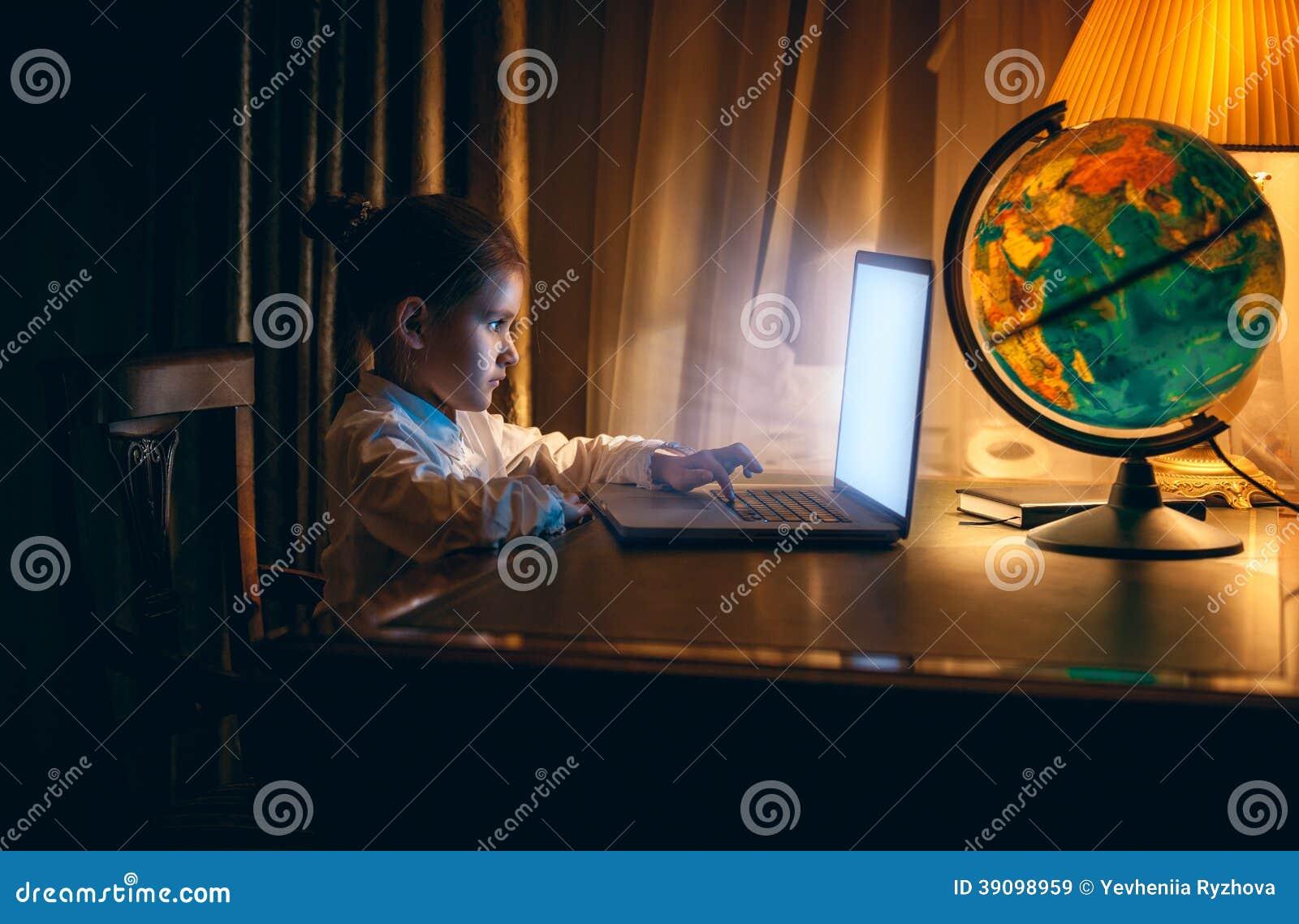 Niña que hace la preparación en el ordenador portátil en la tarde