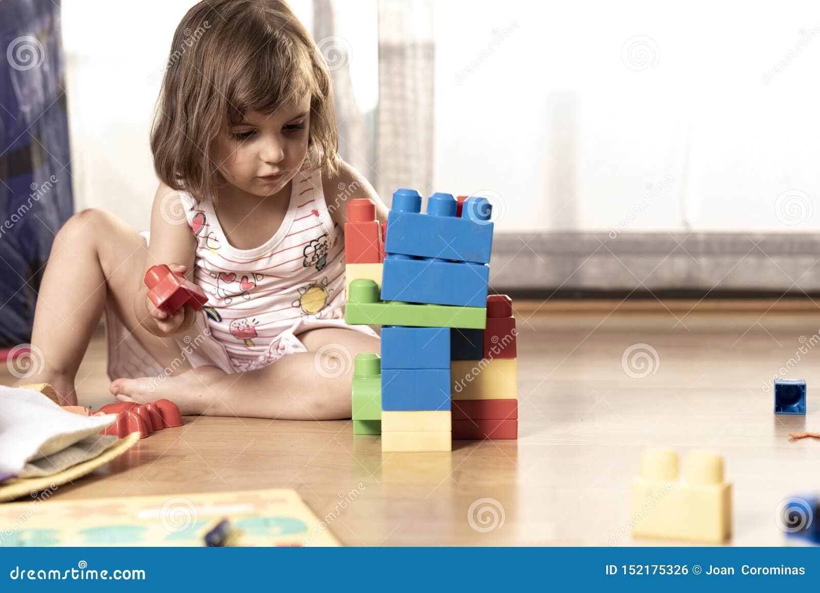Niña que juega con los juguetes del bloque