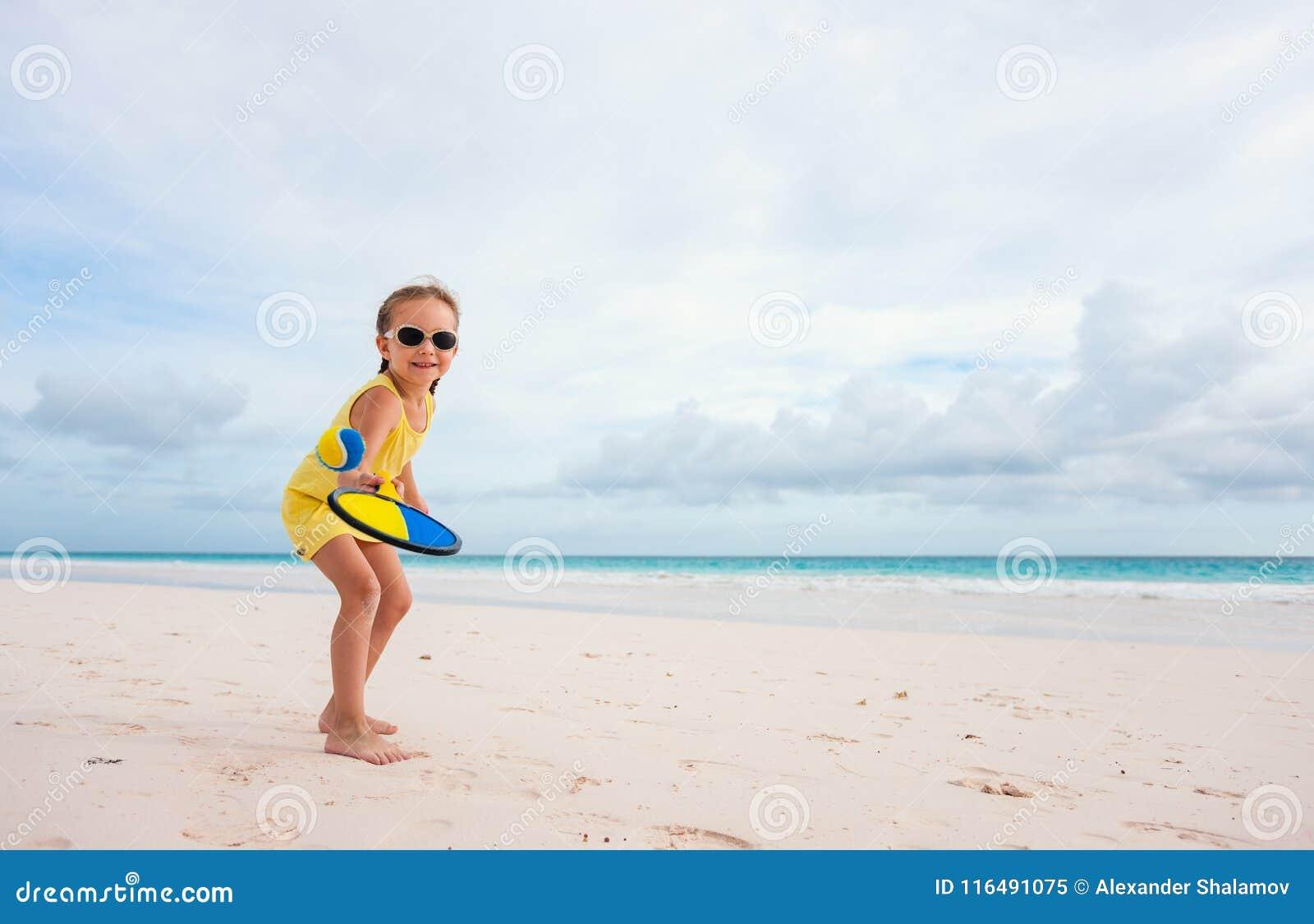 Niña que juega a tenis de la playa