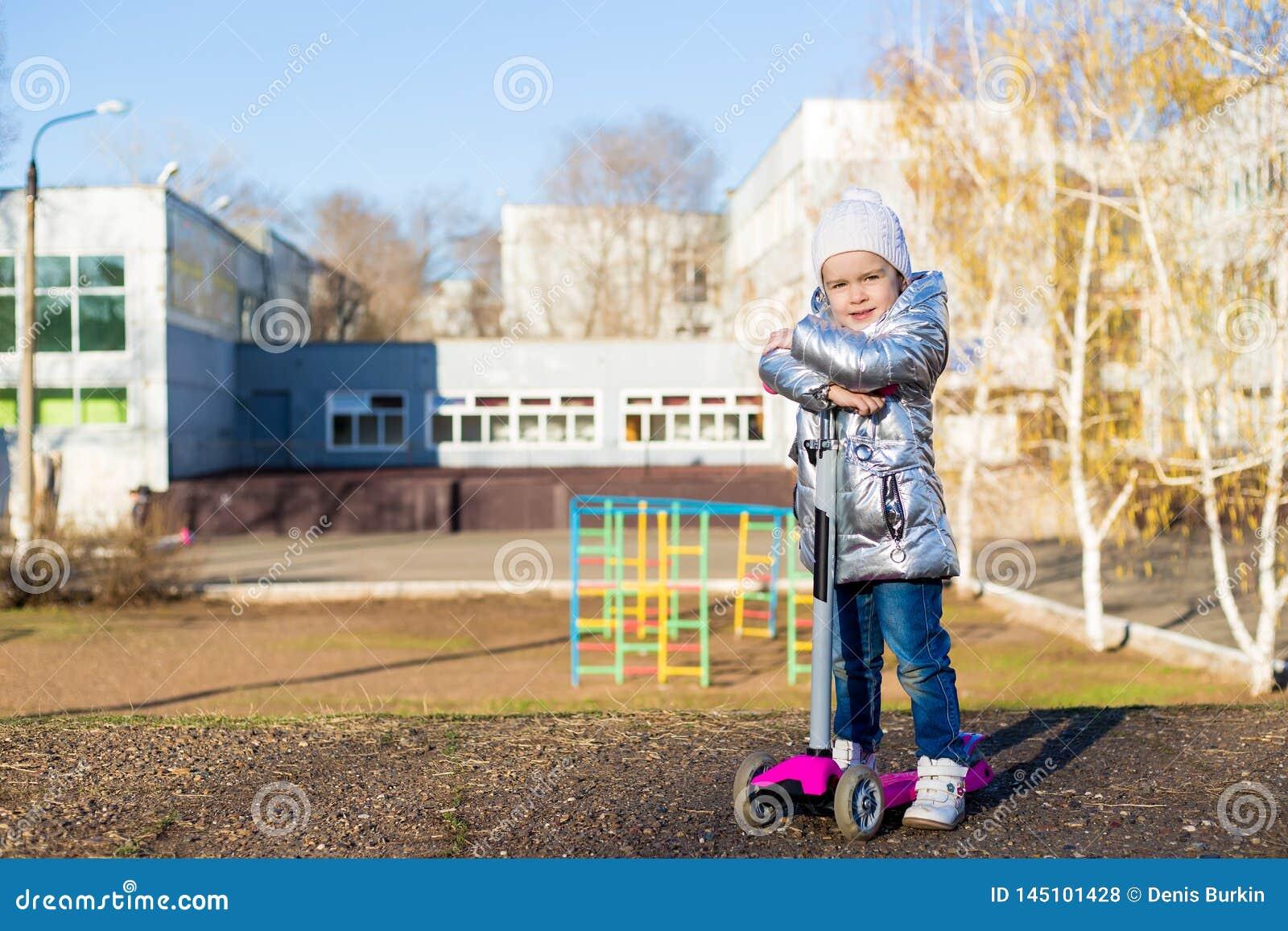 Ni?a que monta una vespa en el parque en un d?a de primavera soleado Ocio activo y deporte al aire libre para los ni?os