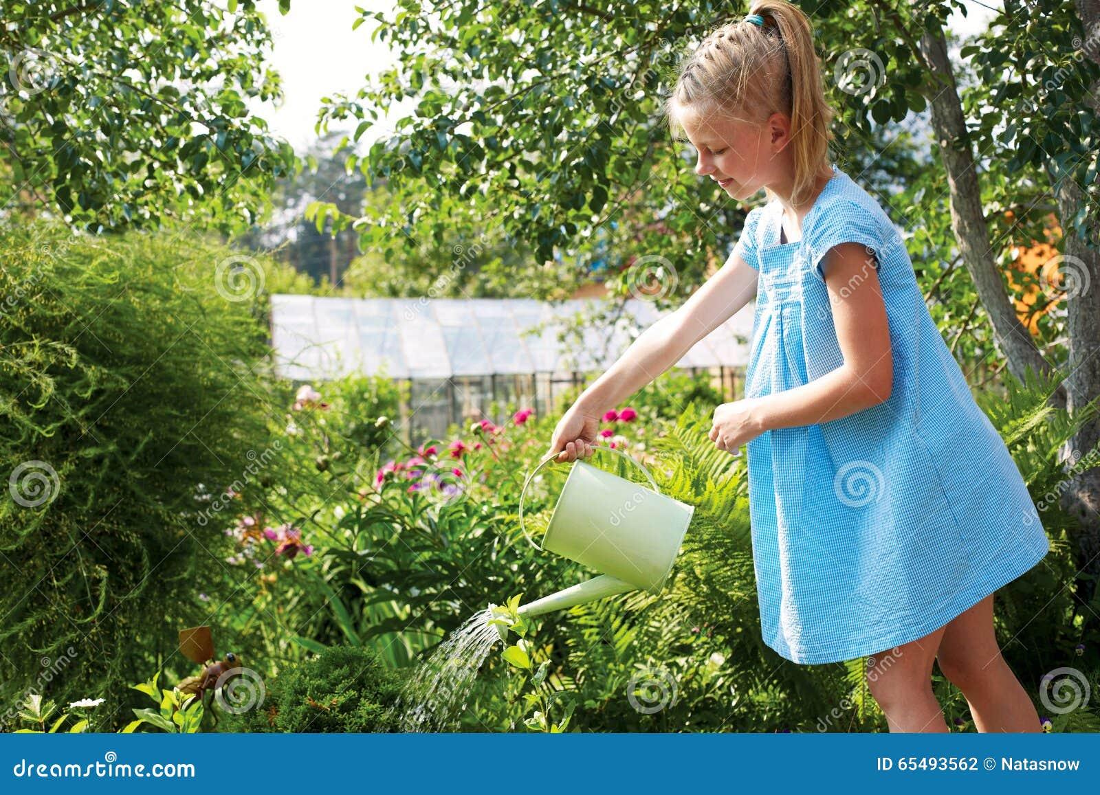 Niña que riega las flores en el jardín de la familia en un summe