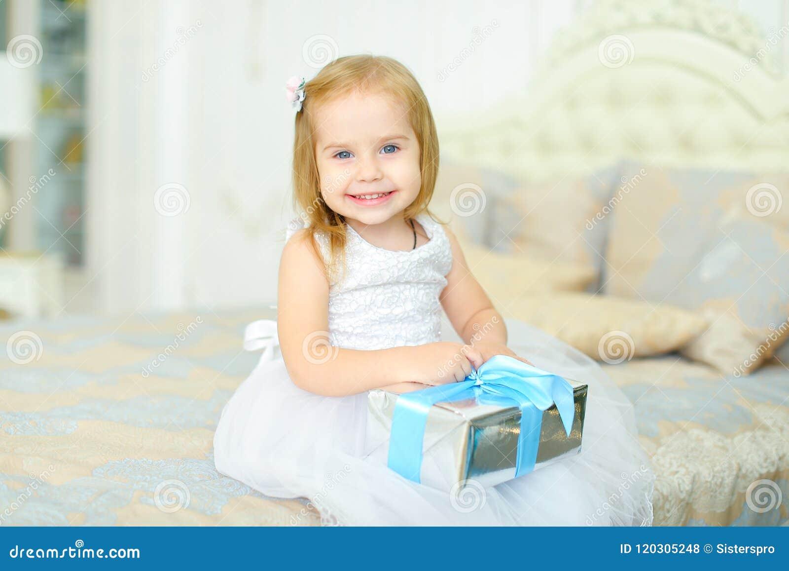 Niña que se sienta en cama con el presente y el vestido blanco que lleva