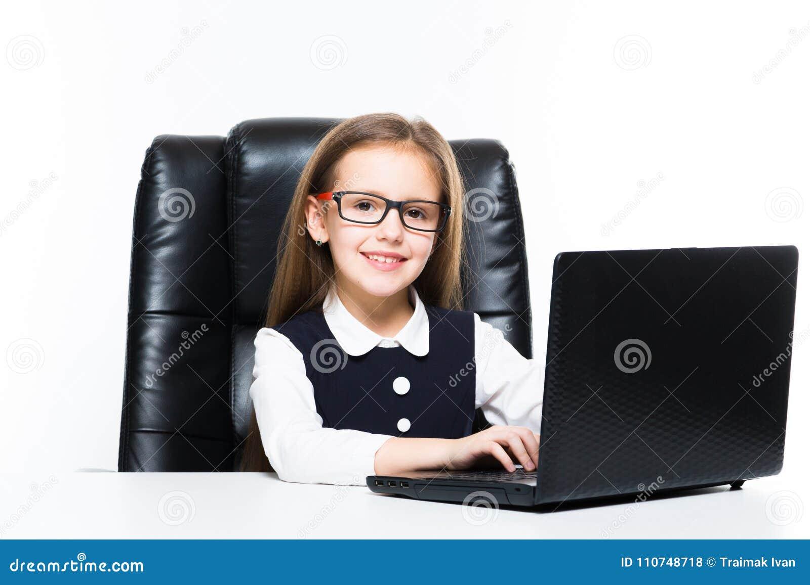 a4dfbce2c La niña sonriente linda adorable que mira in camera sentarse en silla en la  oficina que trabaja en el ordenador portátil vestido como empresaria en  confiado ...