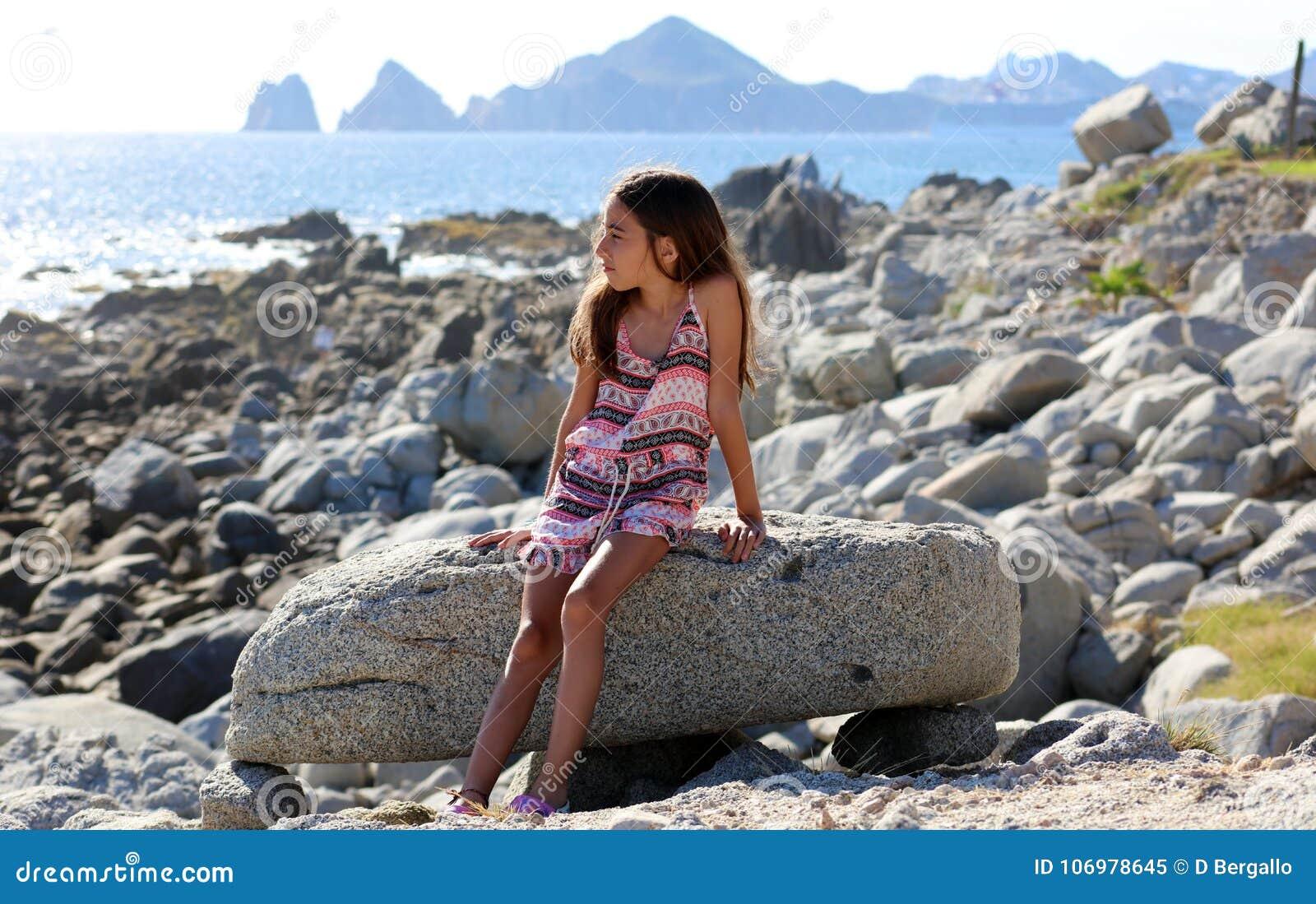 Niña que se sienta en las rocas en el frente de océano en el mar del acantilado del centro turístico de Los Cabos México