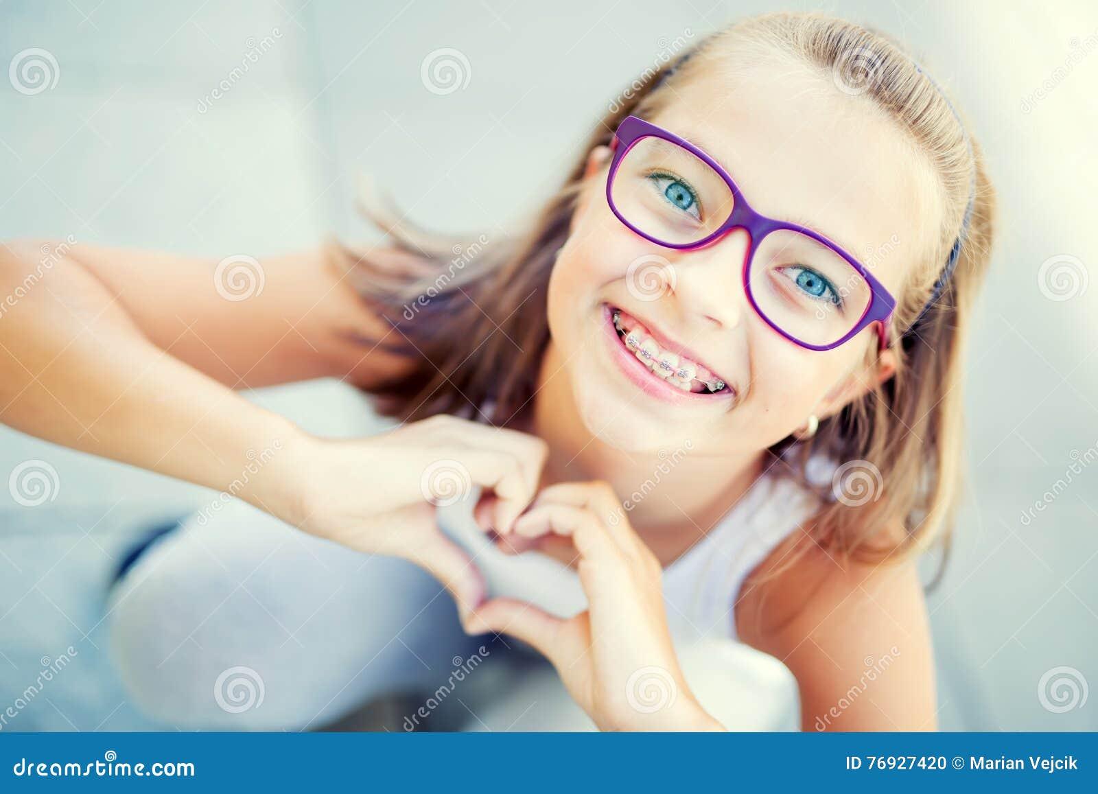 Niña sonriente adentro con los apoyos y los vidrios que muestran el corazón con las manos