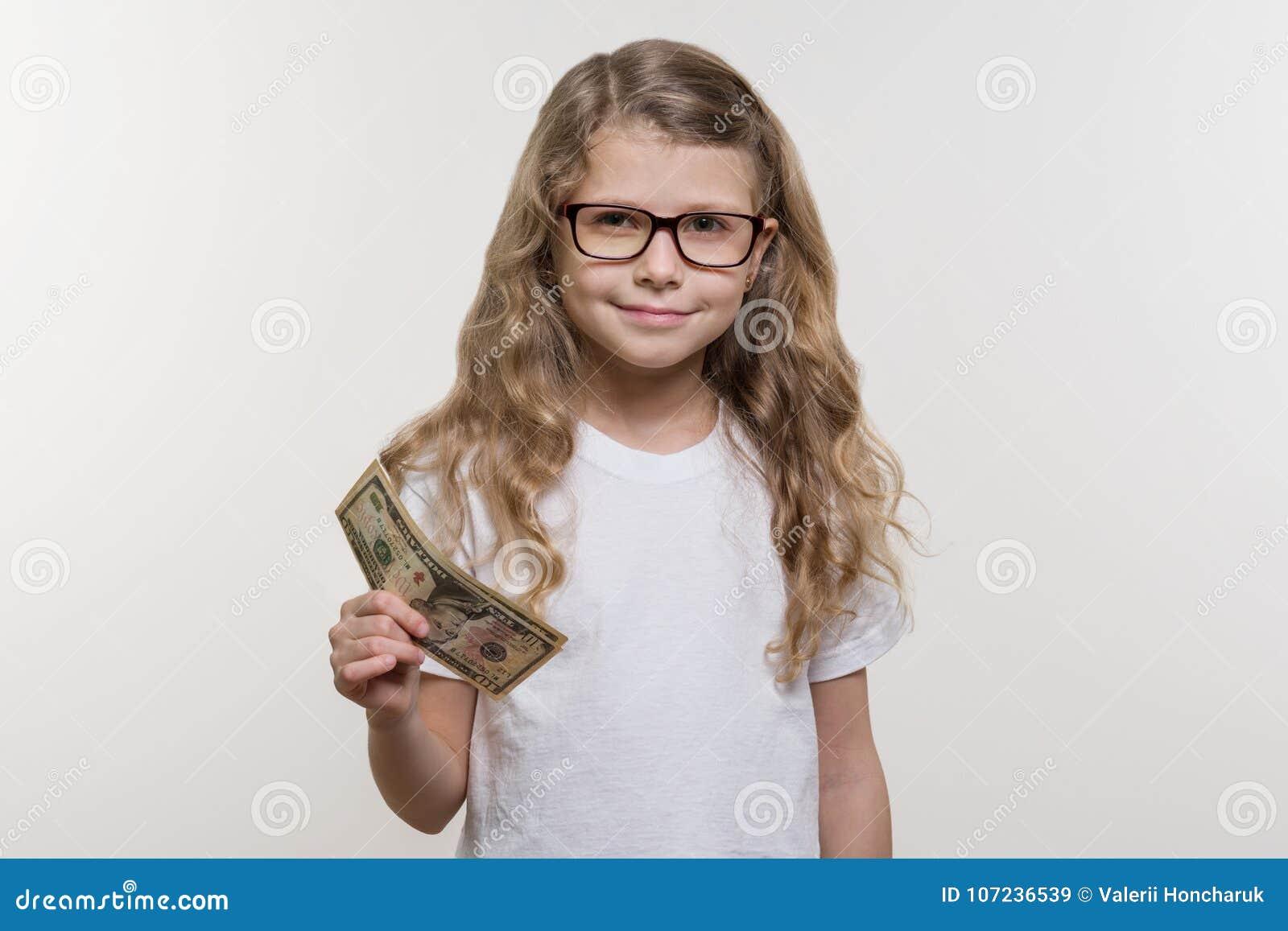 Niña sonriente con efectivo, dinero, finanzas y el concepto de gente