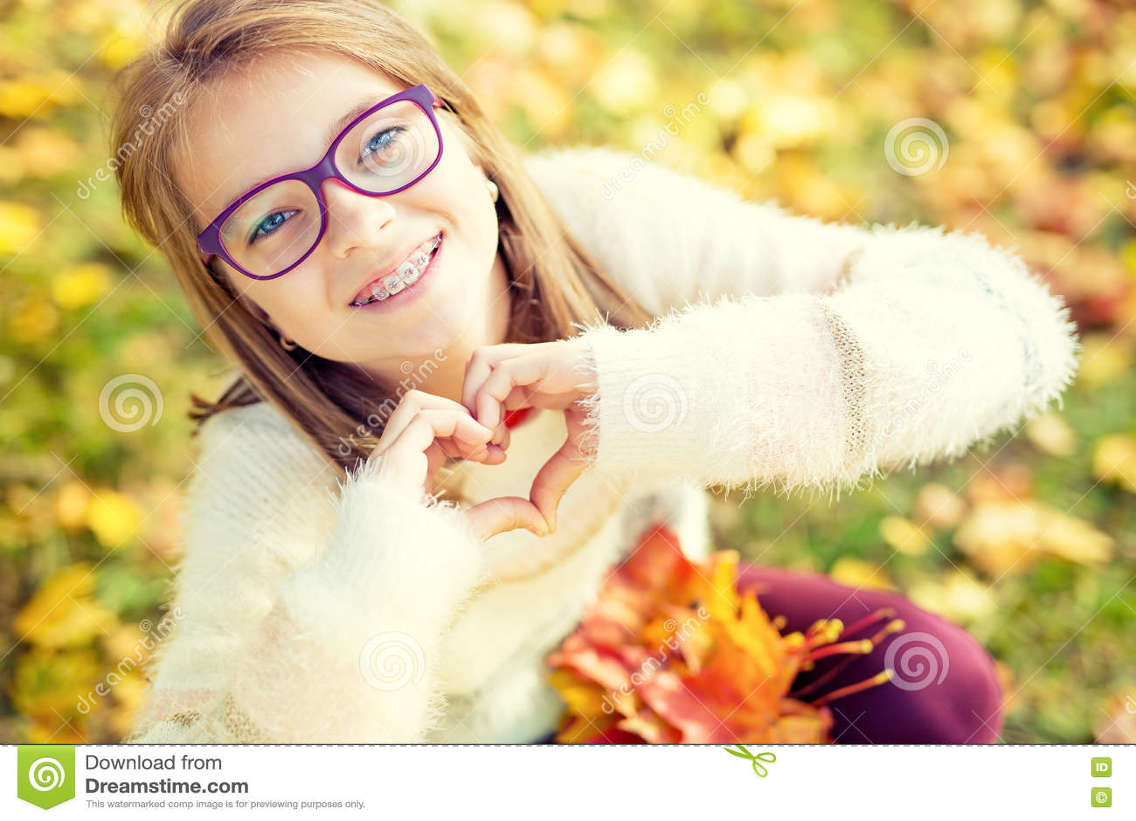 Niña sonriente con los apoyos y los vidrios que muestran el corazón con las manos Tiempo de Autum
