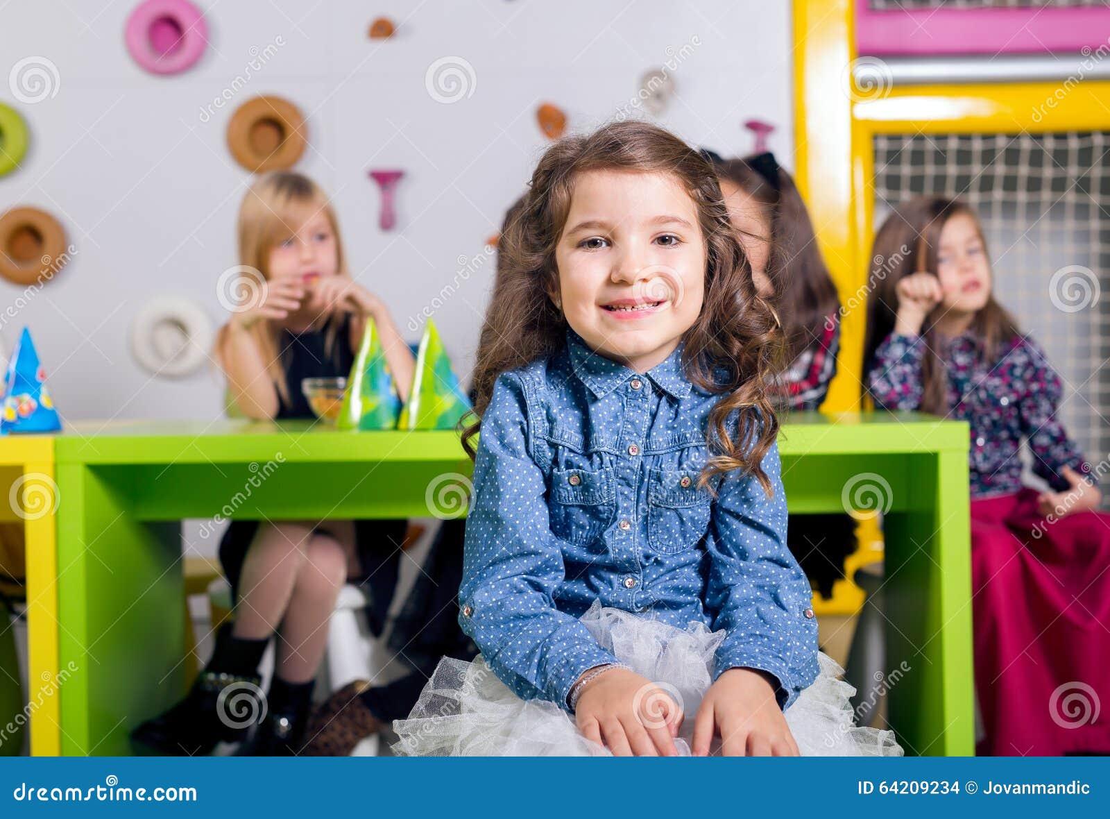 Niña sonriente con sus amigos en la fiesta de cumpleaños