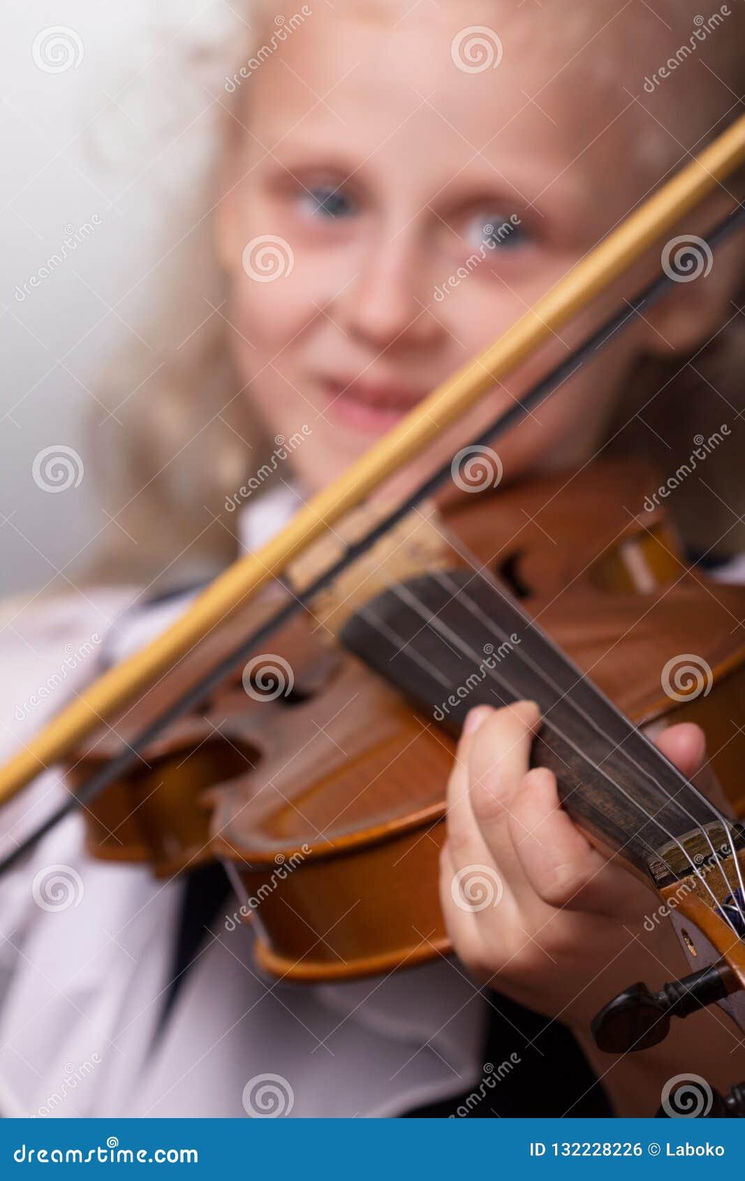 Niña sonriente en la ropa elegante que toca el violín