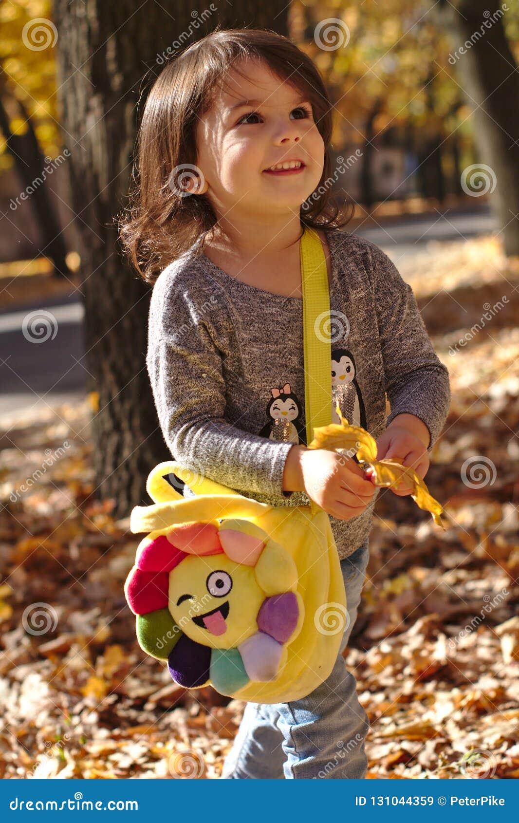 Niña sonriente hermosa en parque del otoño