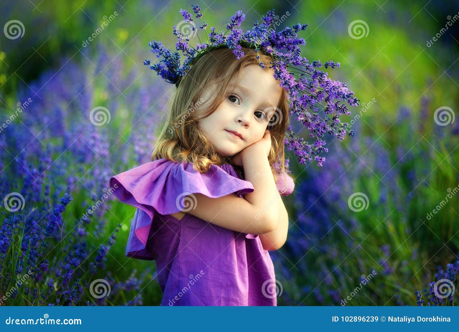 Niña sonriente linda con la guirnalda de la flor en el prado en la granja Retrato del pequeño niño adorable al aire libre
