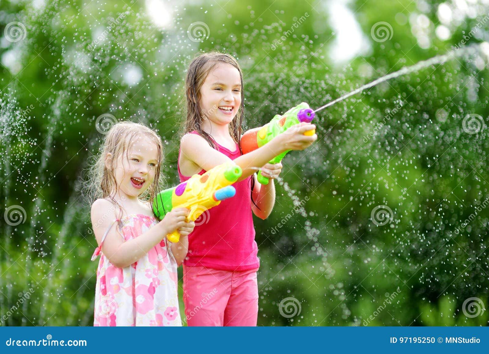 Niñas adorables que juegan con los armas de agua en día de verano caliente Niños lindos que se divierten con agua al aire libre