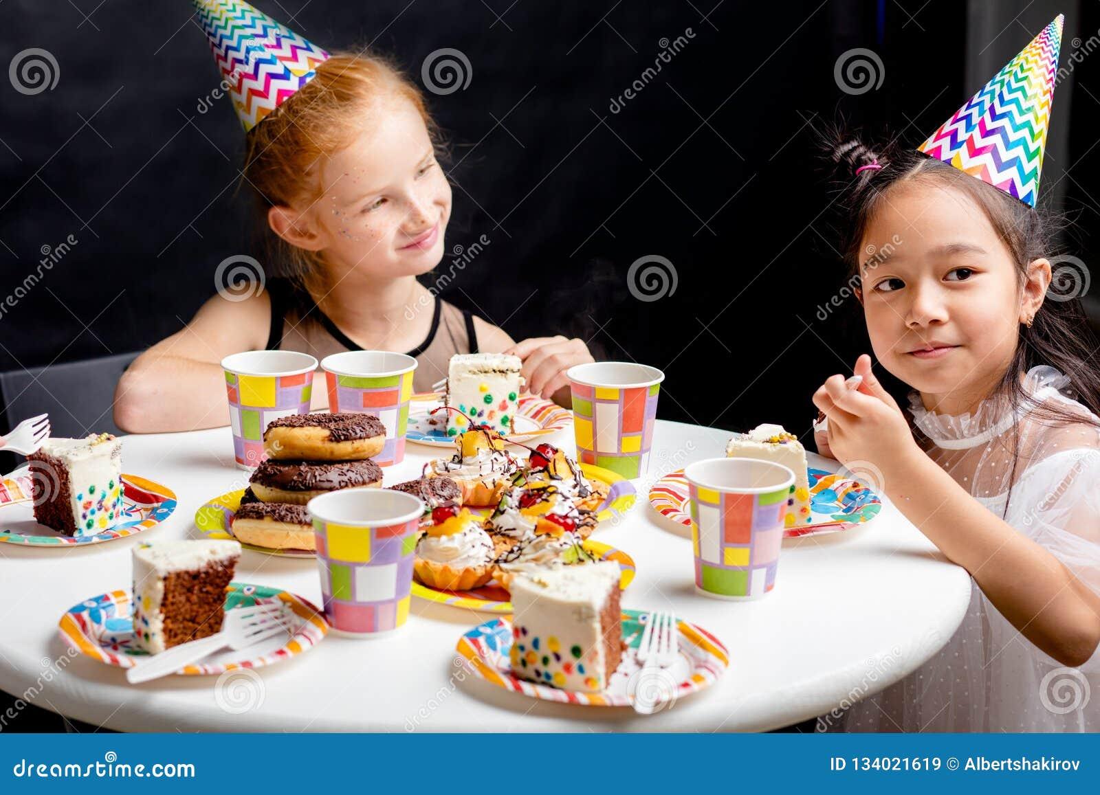 Niñas con el pelo rojo y negro que se sienta en la tabla y enjoing la torta