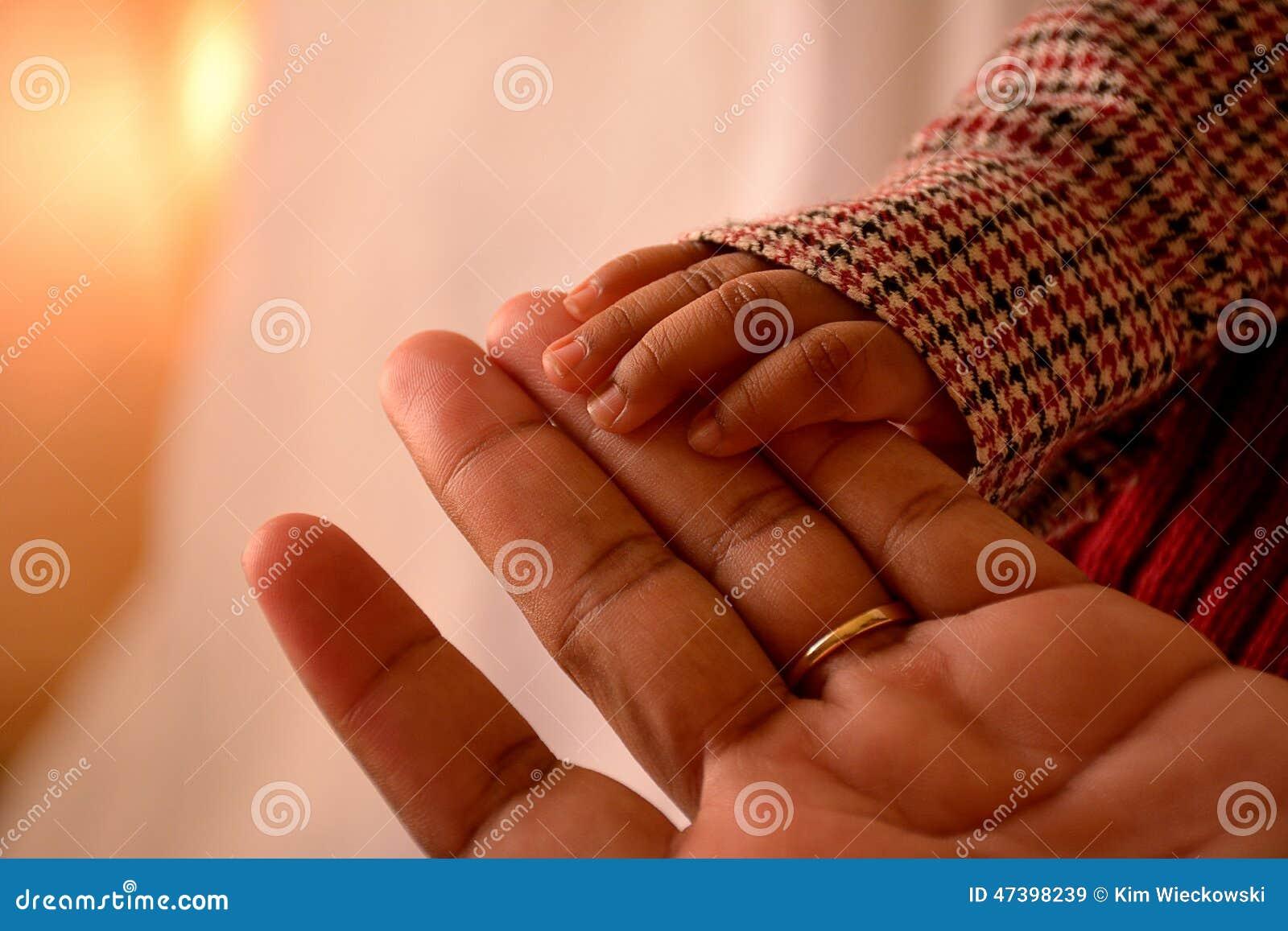 Niño afroamericano y madre que celebran las manos