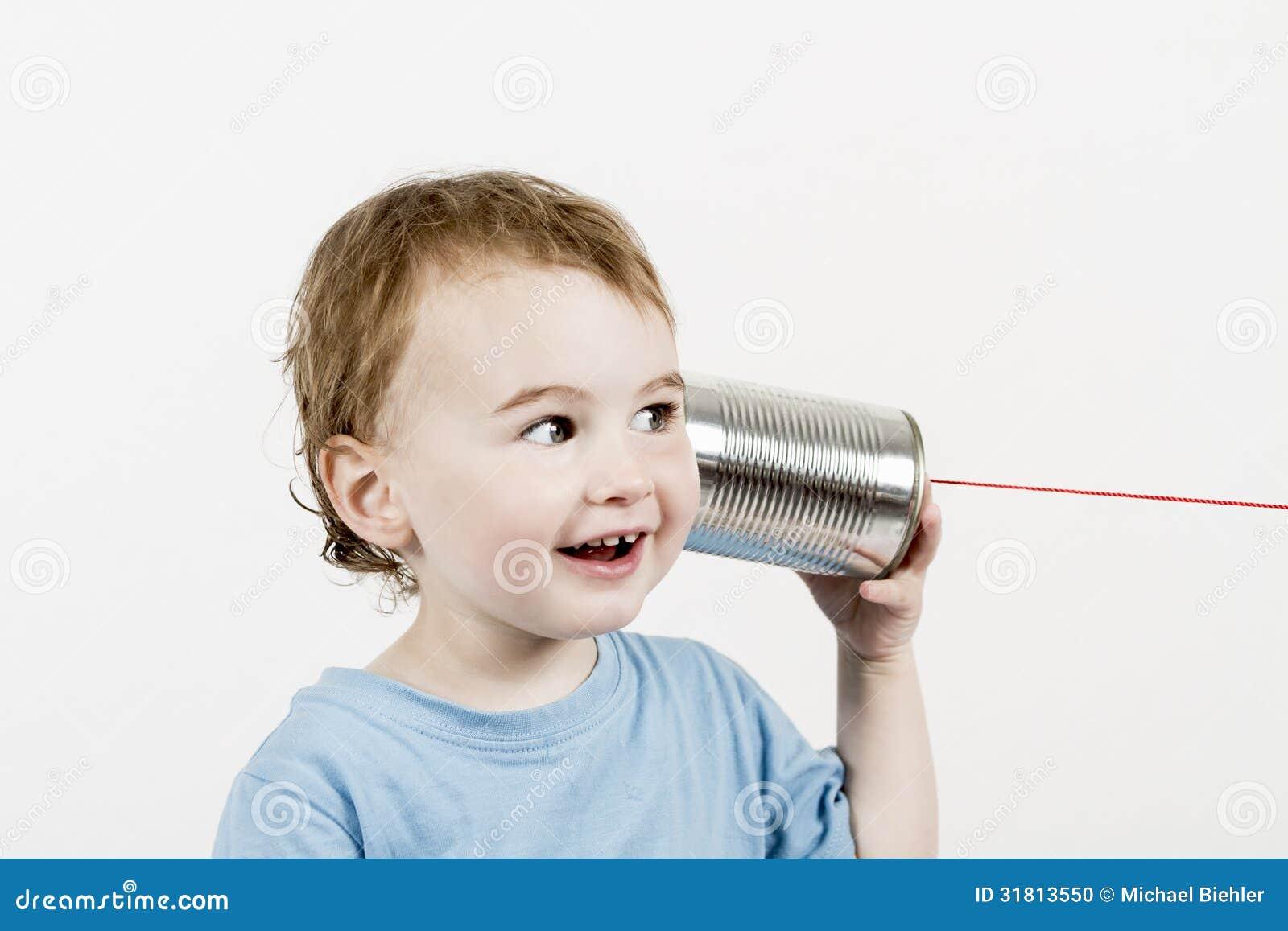 Niño amistoso que escucha el teléfono de la lata