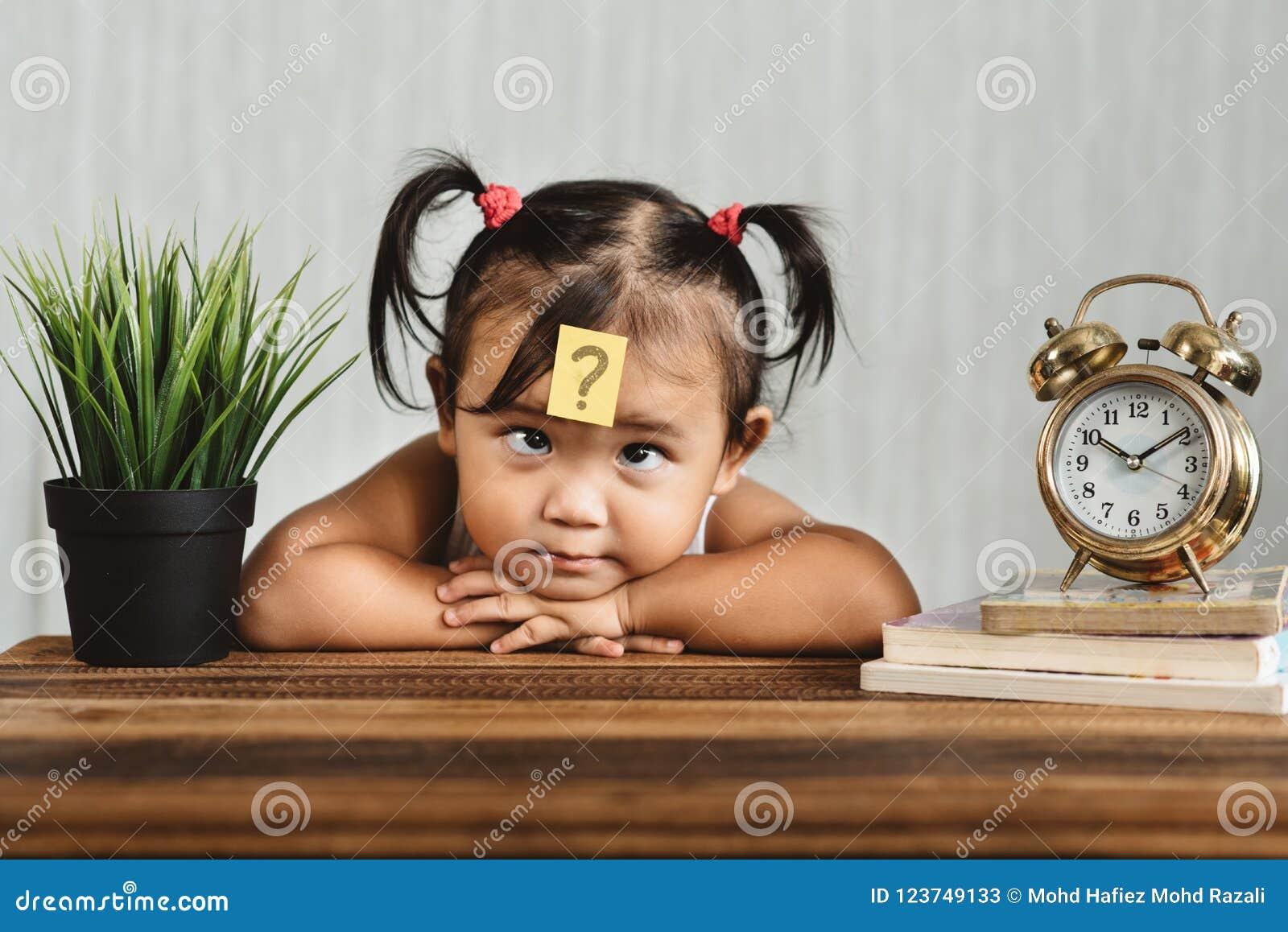 Niño asiático lookian lindo y confuso con el signo de interrogación en su frente