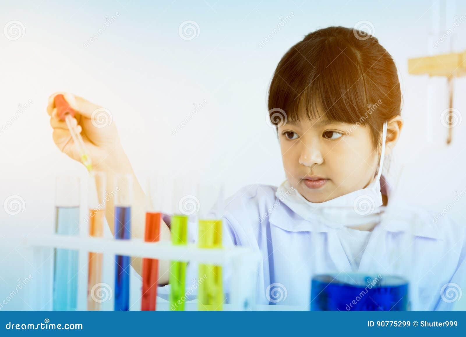 Niño asiático que juega al científico con los tubos coloridos del laboratorio