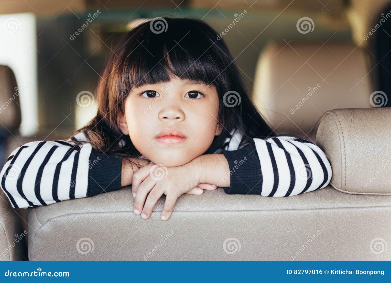 Niño chino asiático deprimido Niña que muestra su cara infeliz en coche