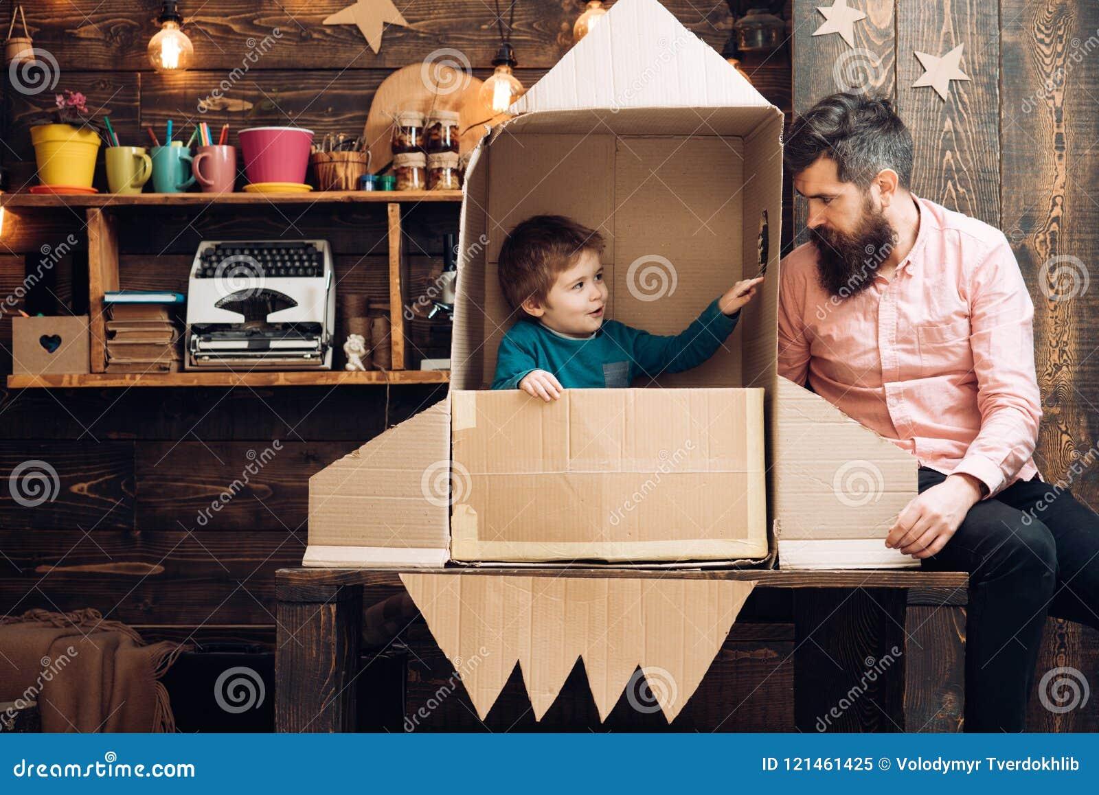 Niño como astronauta con el cohete del juguete que juega y que sueña con hacer astronautas Retrato del niño y del padre divertido
