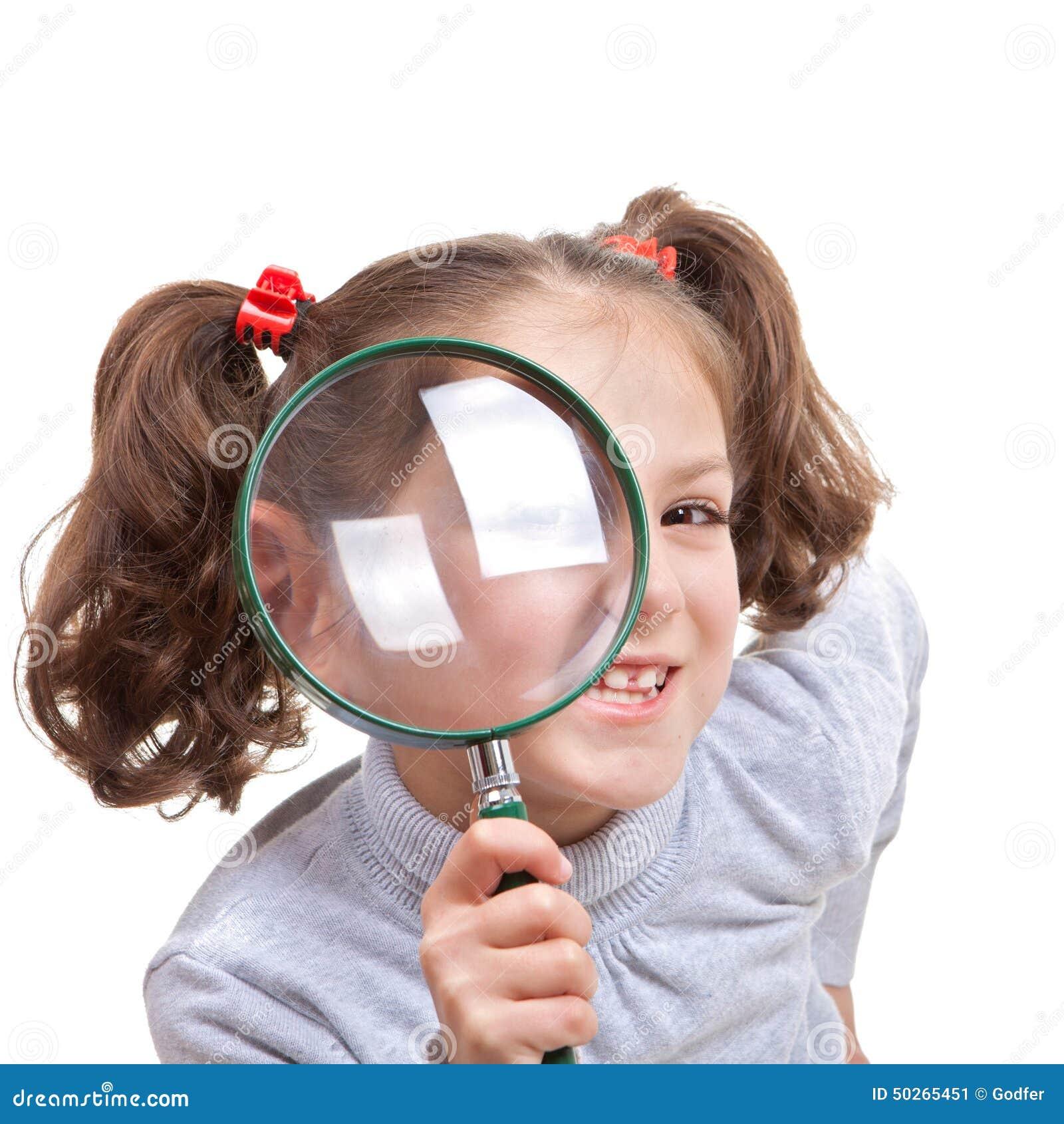 Niño con el vidrio de espía que magnifica