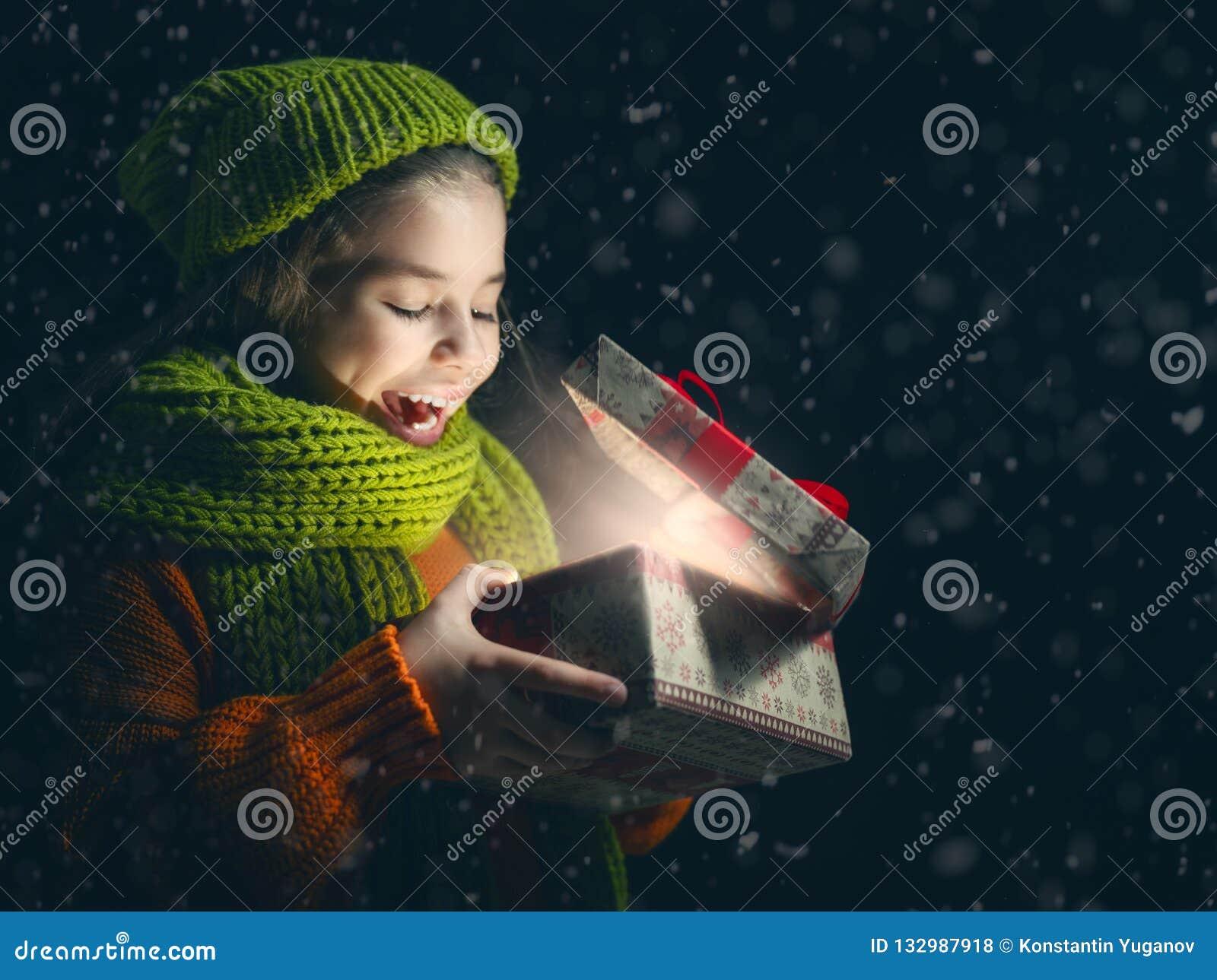 Niño con la caja de regalo en fondo oscuro