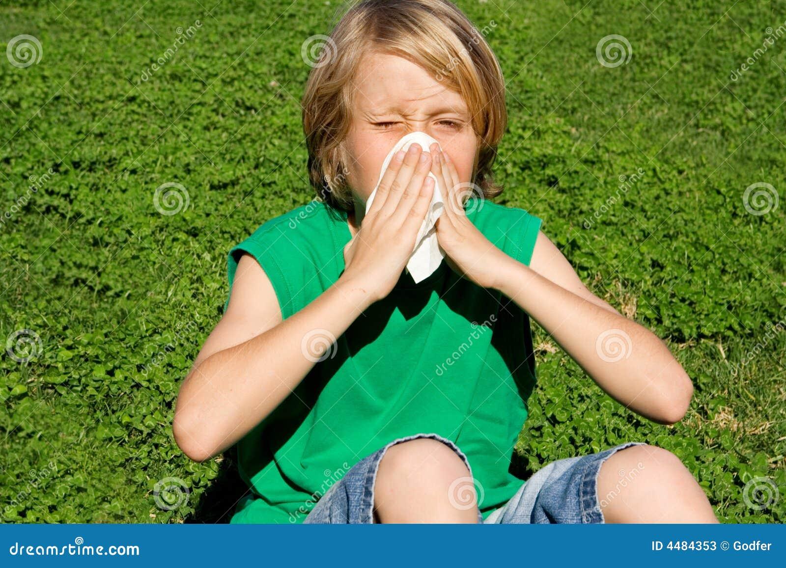 Niño con la nariz que sopla de la alergia