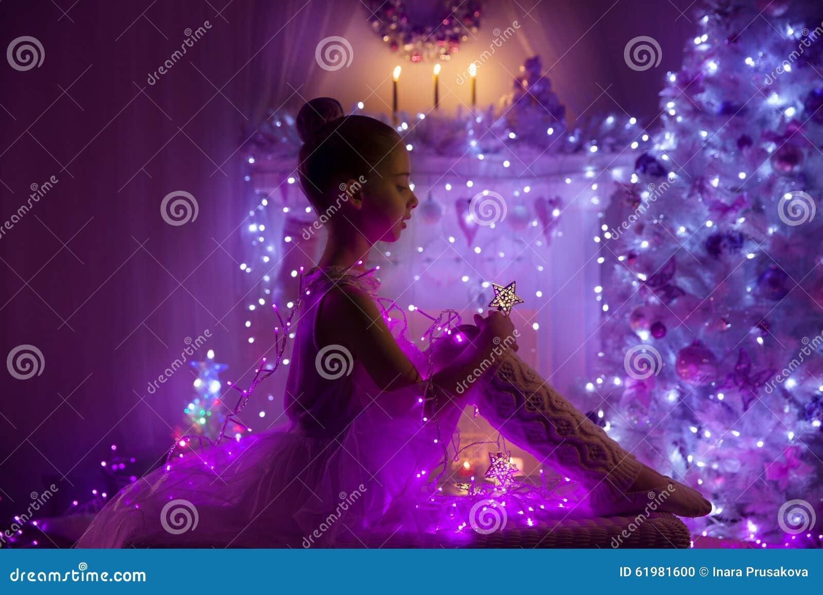 Niño de la muchacha, luces del árbol de navidad, niño en noche del día de fiesta