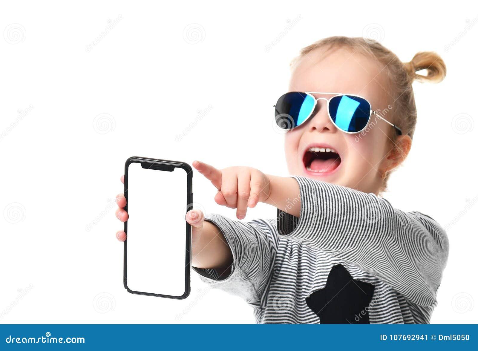 677843ae00 Niño de la niña en las gafas de sol tipo aviador azules que muestran la  pantalla
