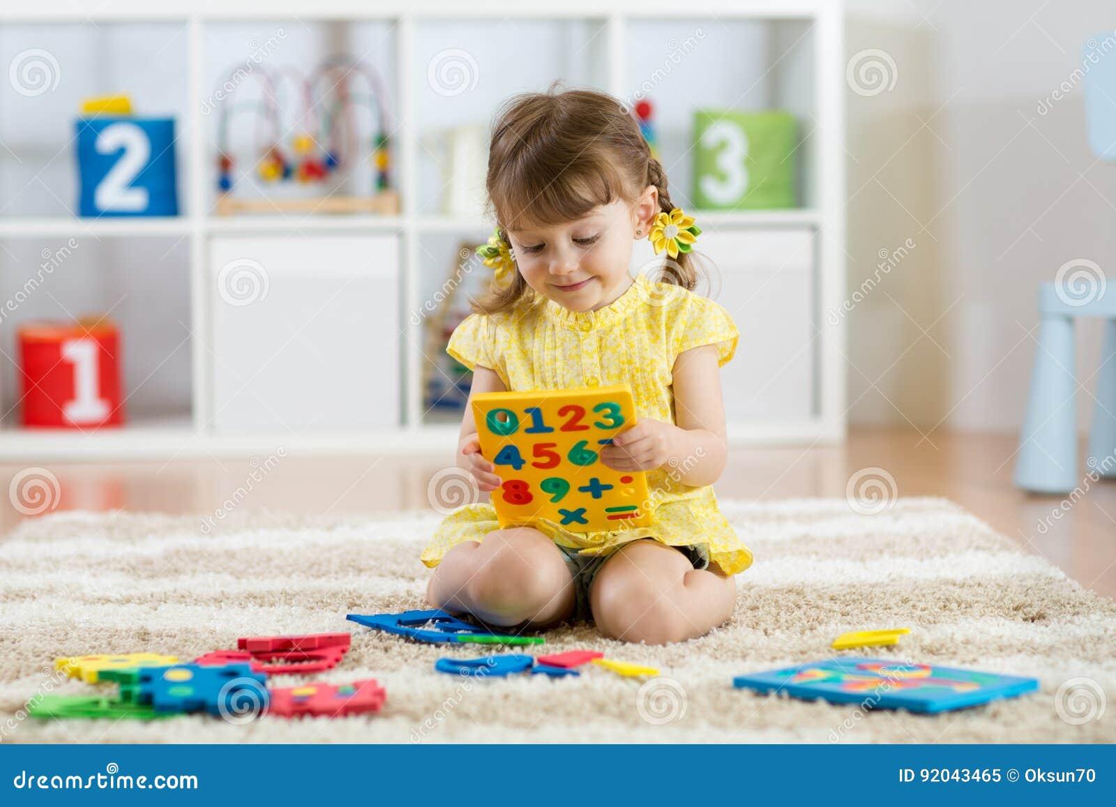 Niño de la niña que juega con las porciones de dígitos o de números plásticos coloridos dentro