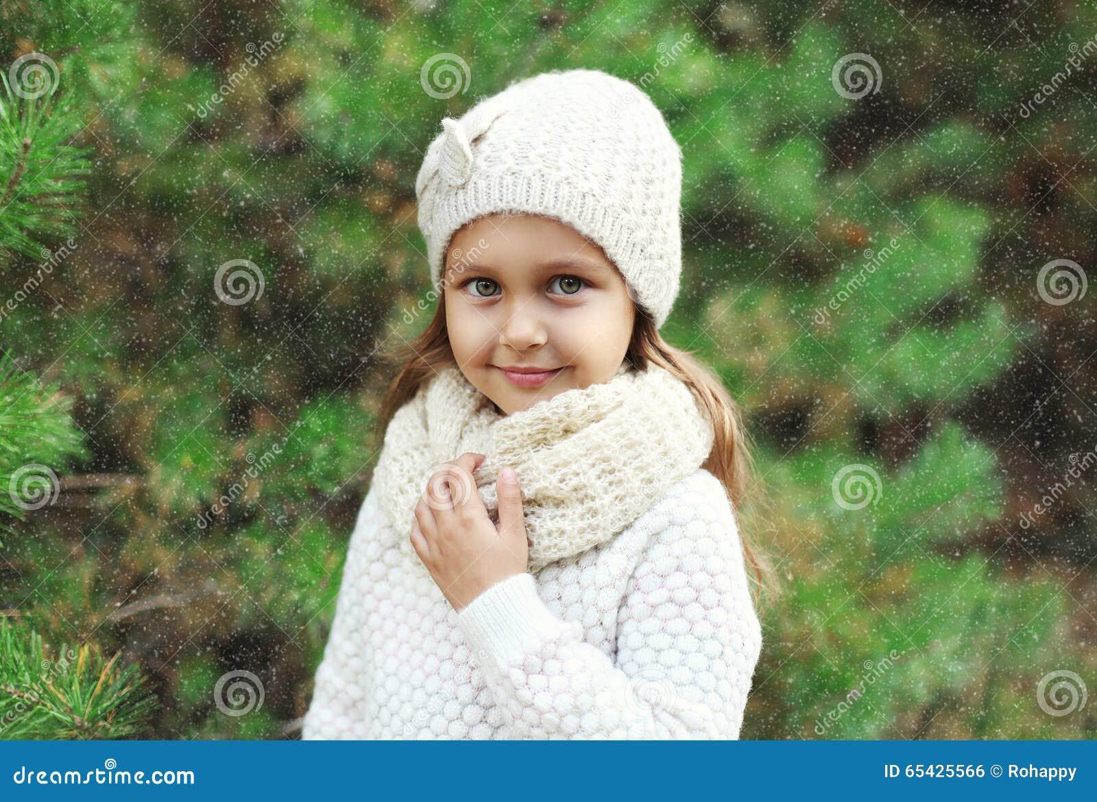 Niño de la niña que lleva el sombrero y el suéter hechos punto con la bufanda cerca del árbol de navidad