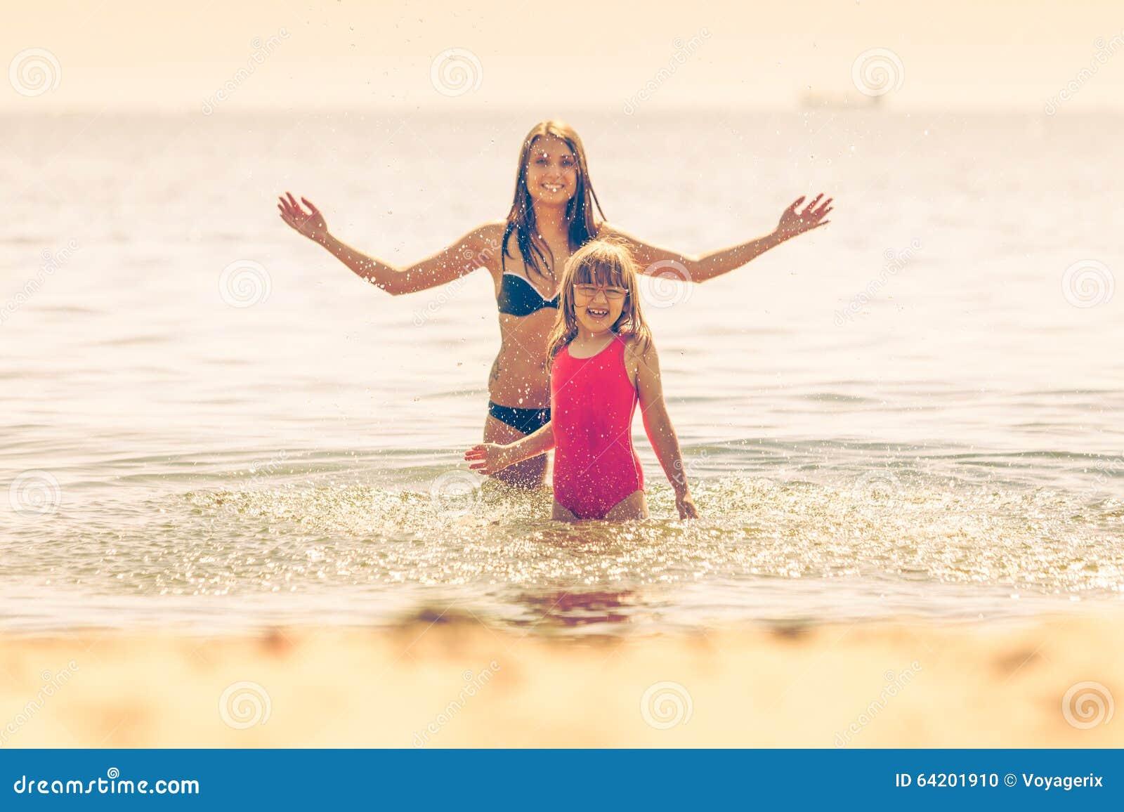 Niño de la niña y madre de la mujer en agua de mar Diversión
